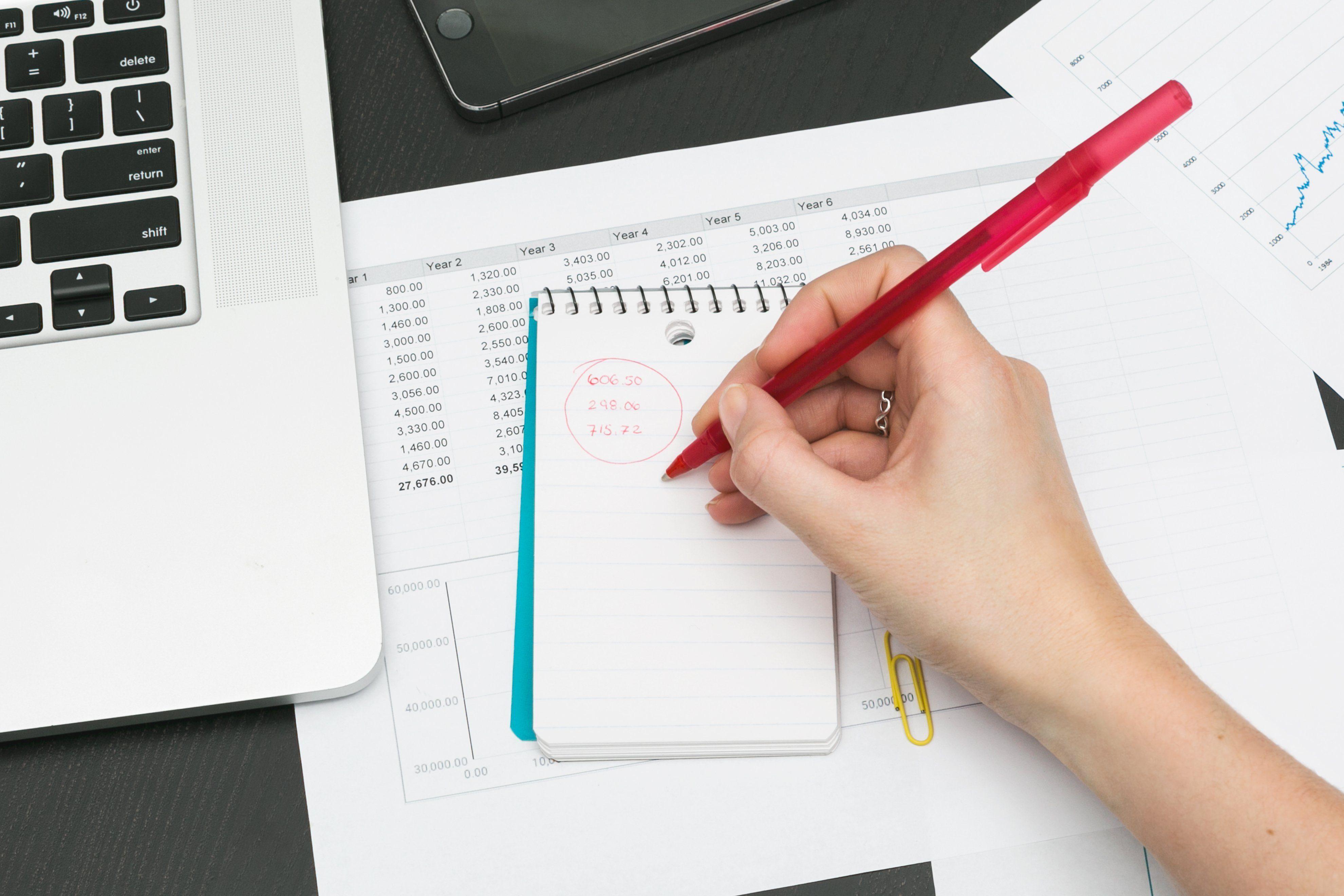 Frau schreibt in einen Notizblock