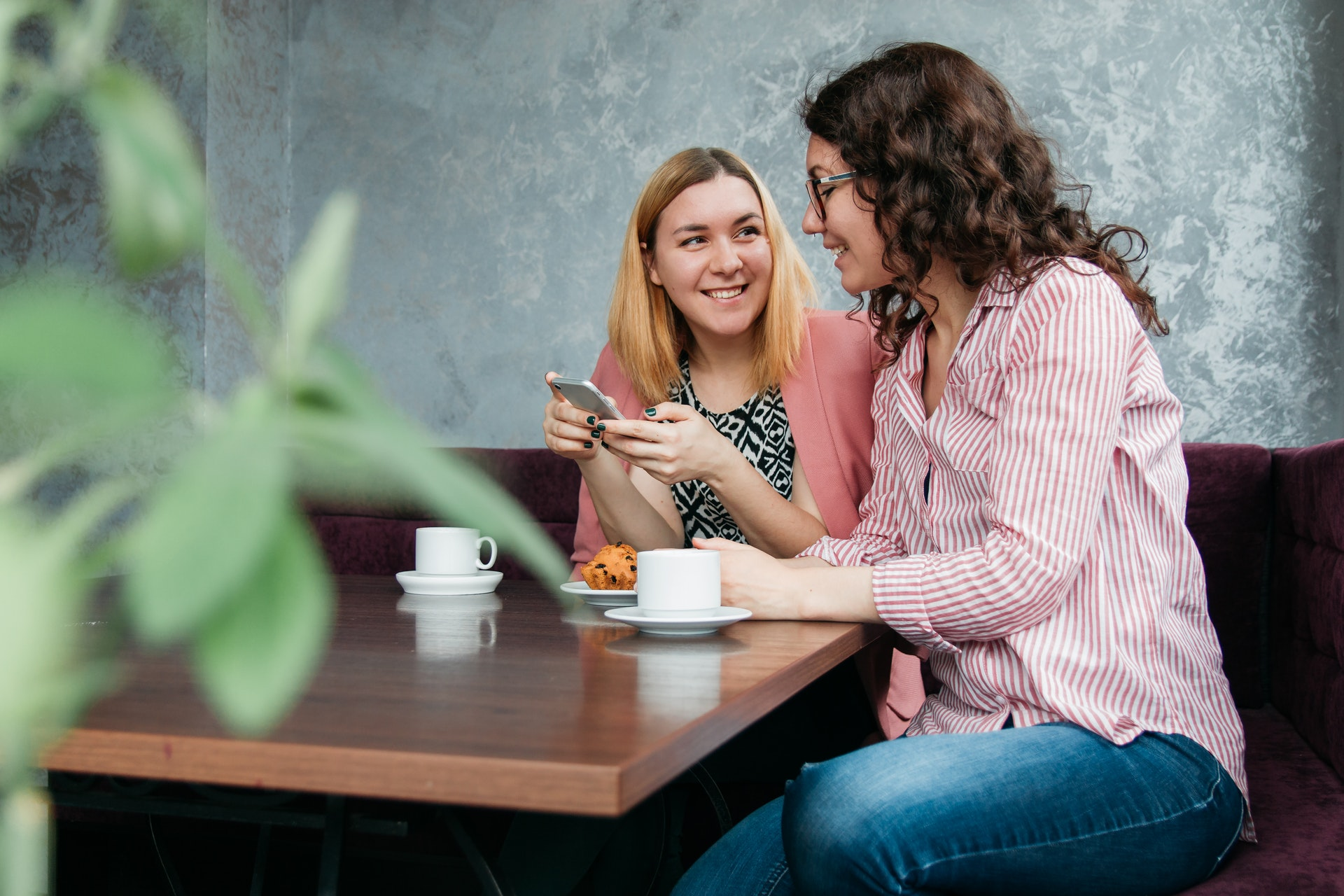 empatia e intelligenza emotiva: delle amiche ridono con lo smartphone