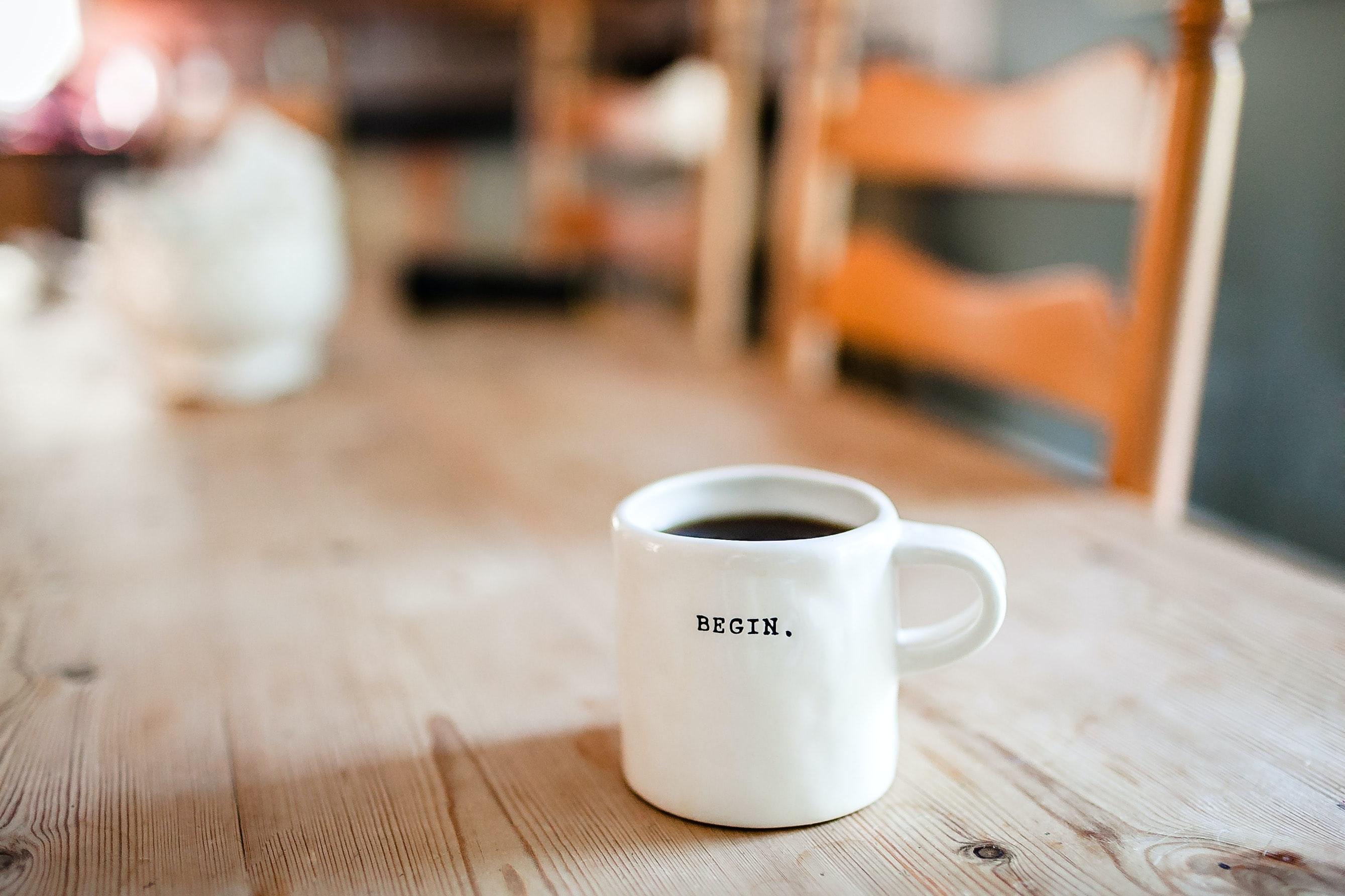 """Une tasse de café sur laquelle est écrit """"begin"""""""