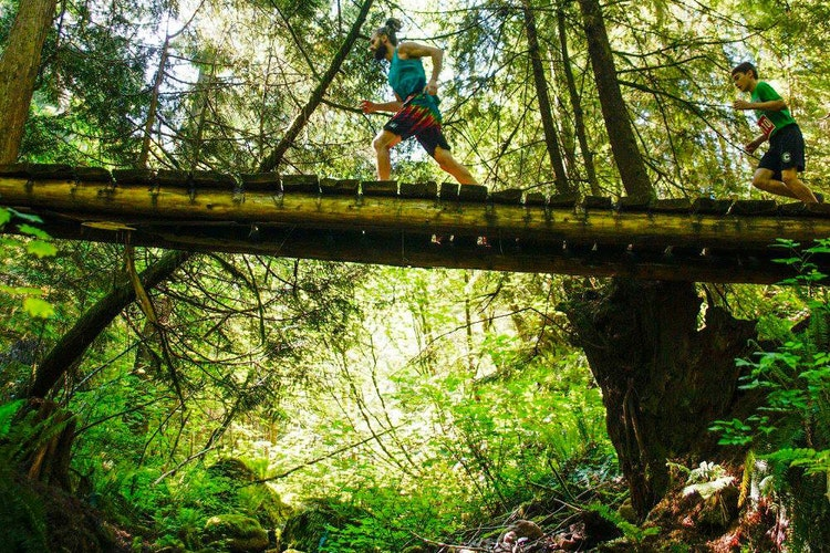Trail runners crossing a wooden bridge over a stream in a wooded forest
