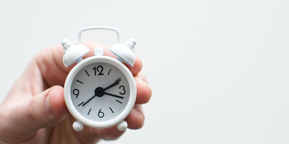 hand holding an alarm clock