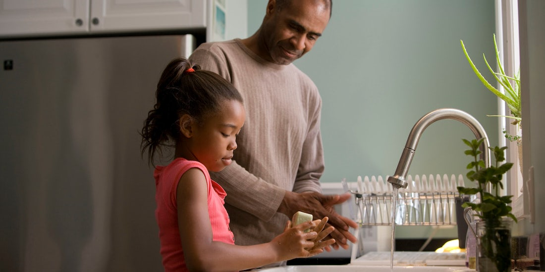 Father and daughter at kitchen sink