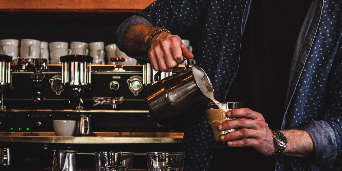 male pouring a latte in a bar