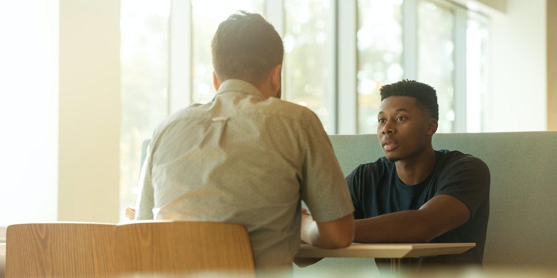 Redundancy meeting, two people talking in a light office