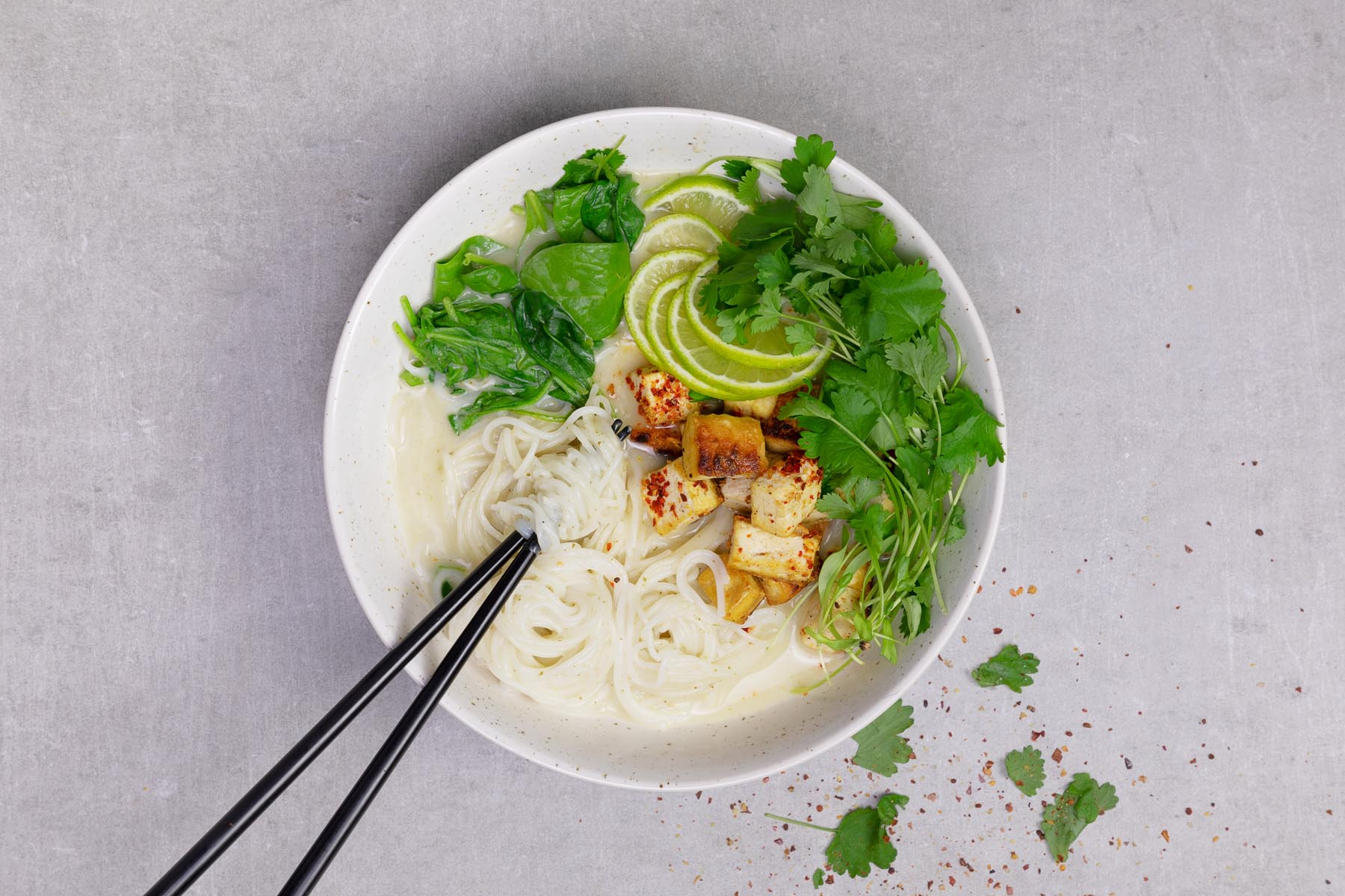 Fried tofu and green curry sit atop a bowl of rice noodles.