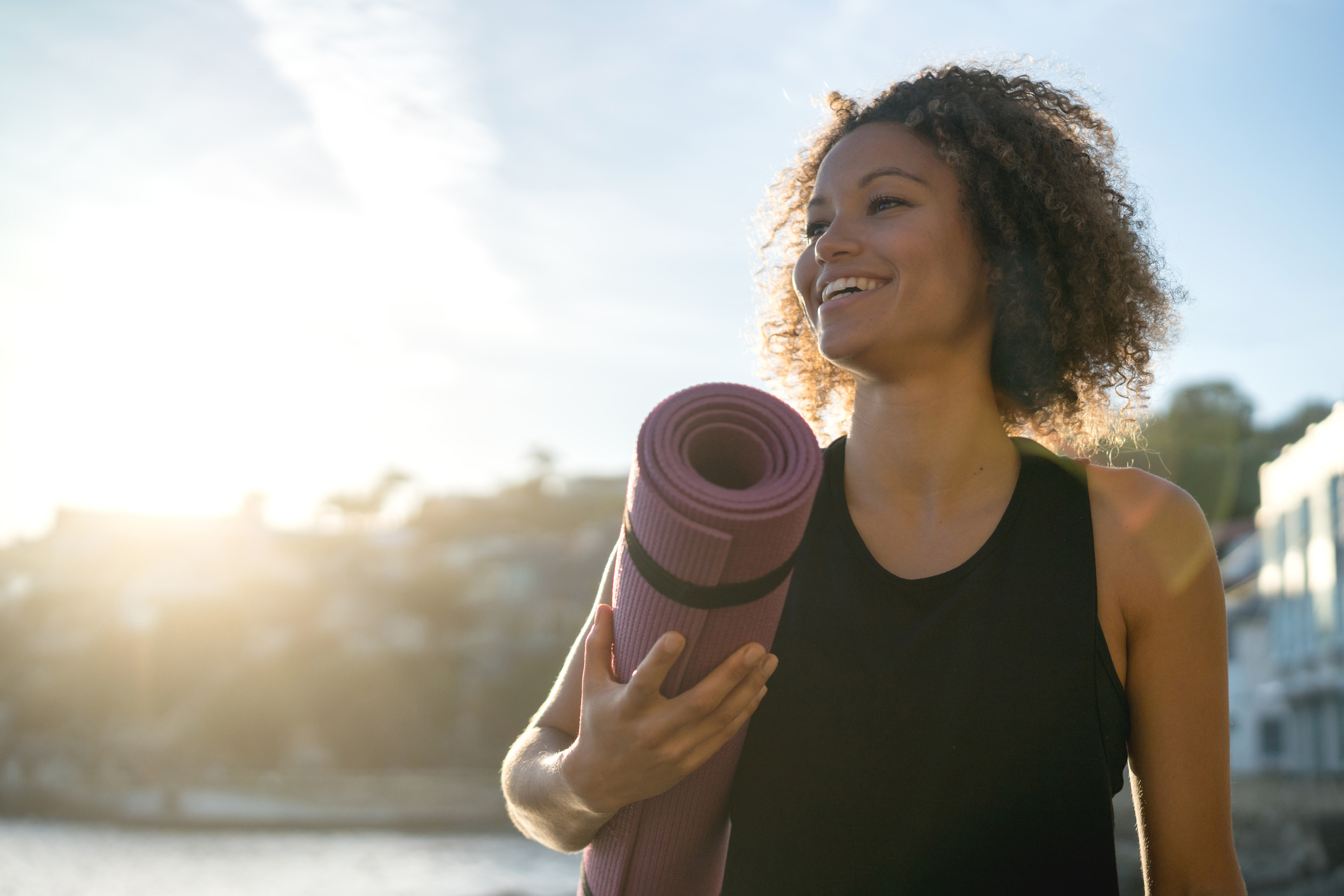 Happy woman holding a yoga mat at the beach