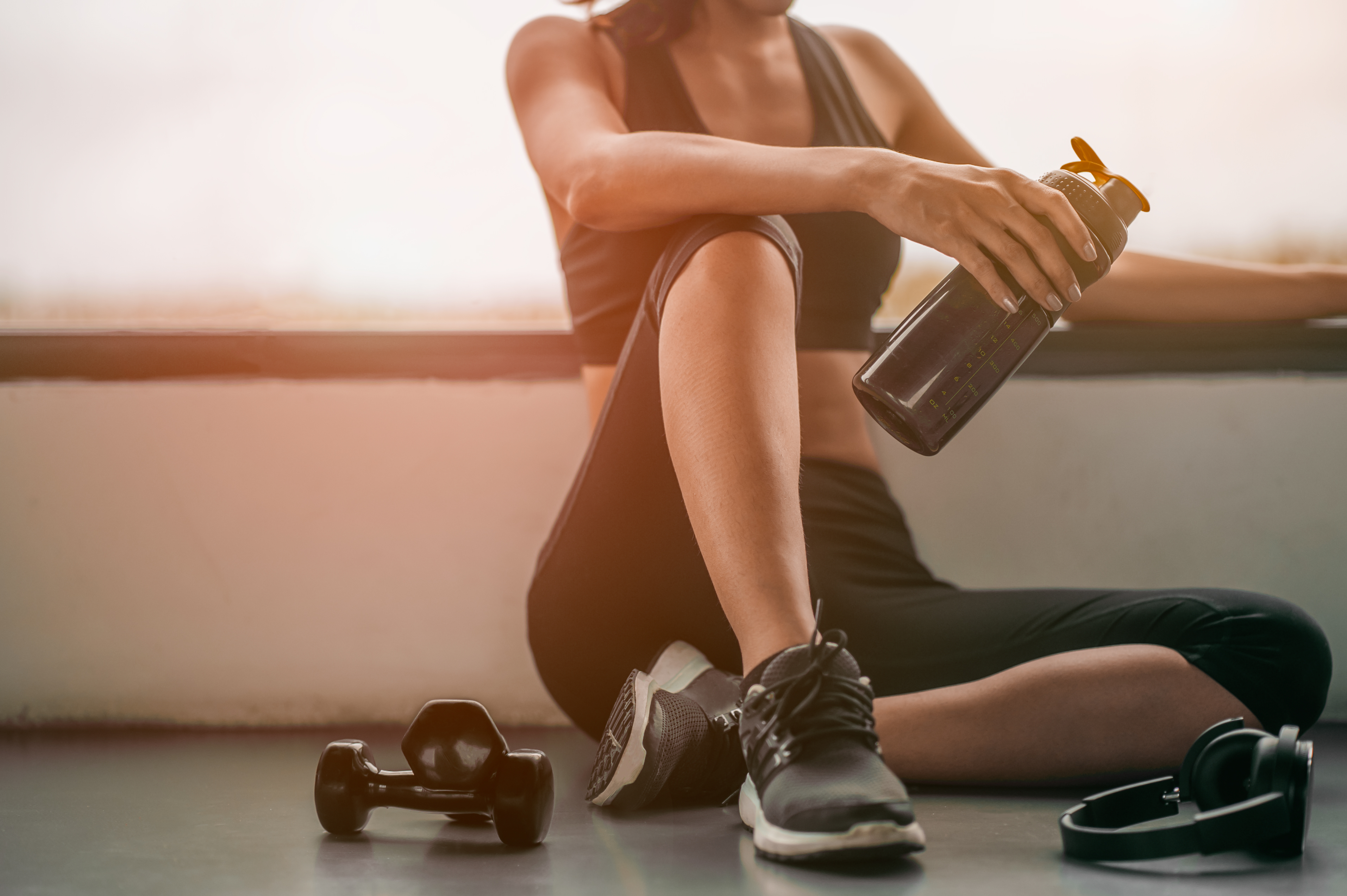 Woman relaxing after a workout and drinking whey protein