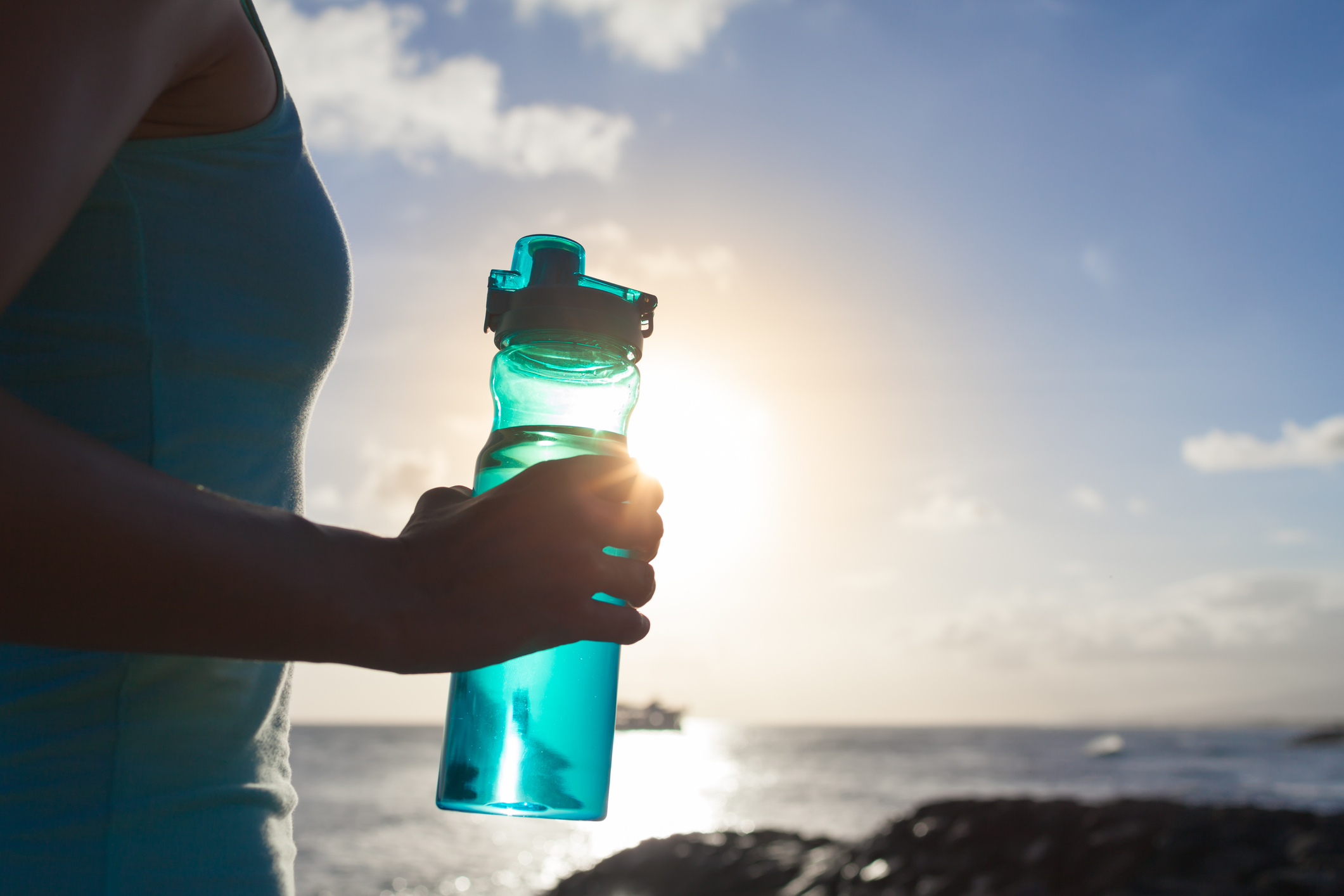 Person holding a water bottle outdoors after workout