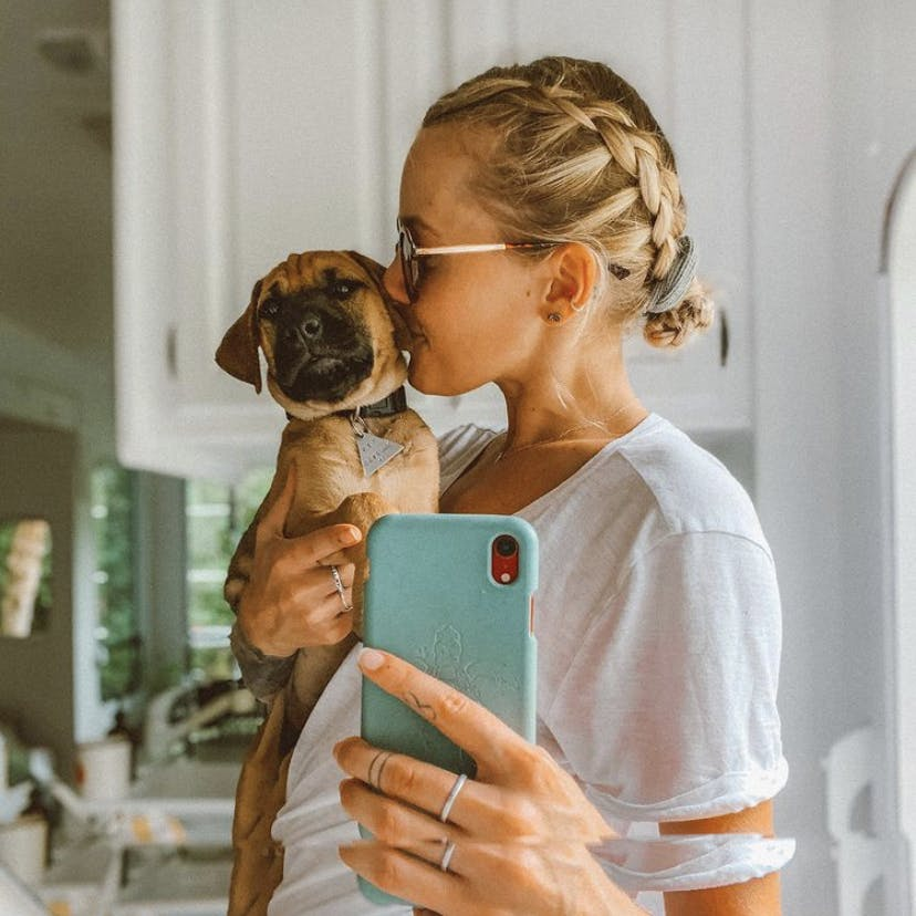Woman with dog and biodegradable eco-friendly Pela phone case