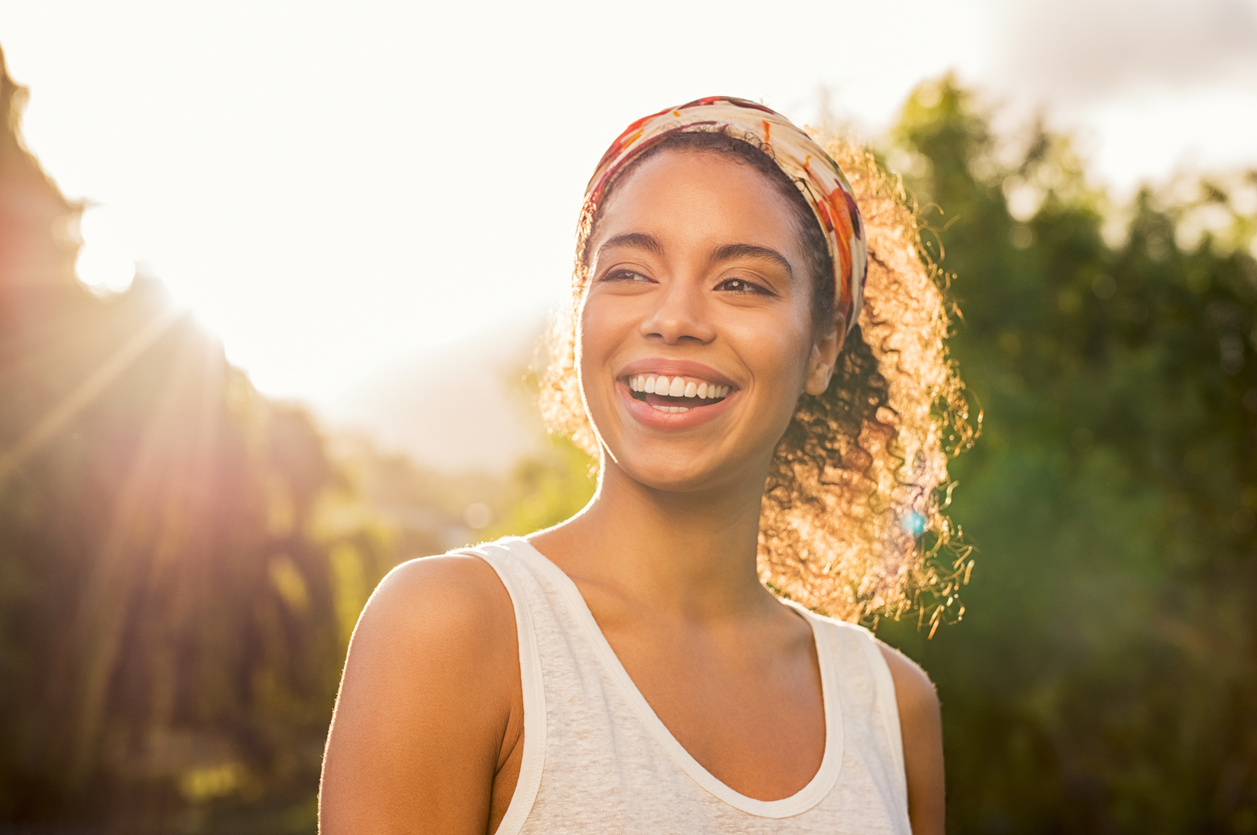 beautiful woman smiling with the sun behind her
