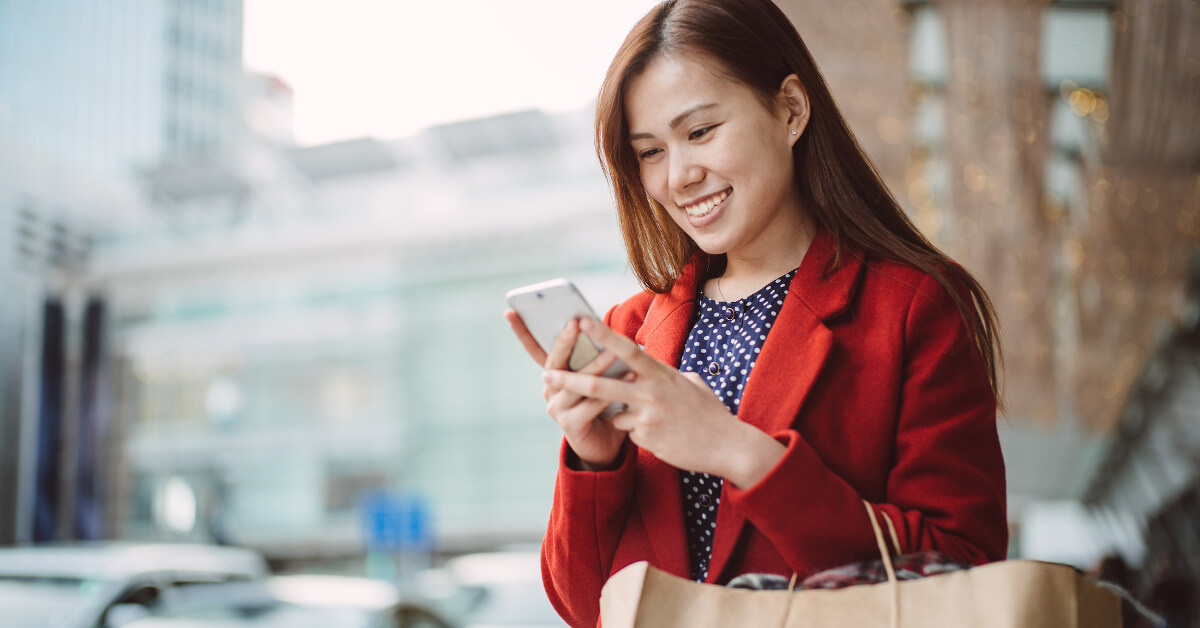 Woman in Red Coat with Shopping Bag and Smartphone
