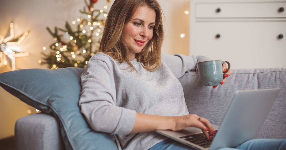 Woman online shopping and holding a mug