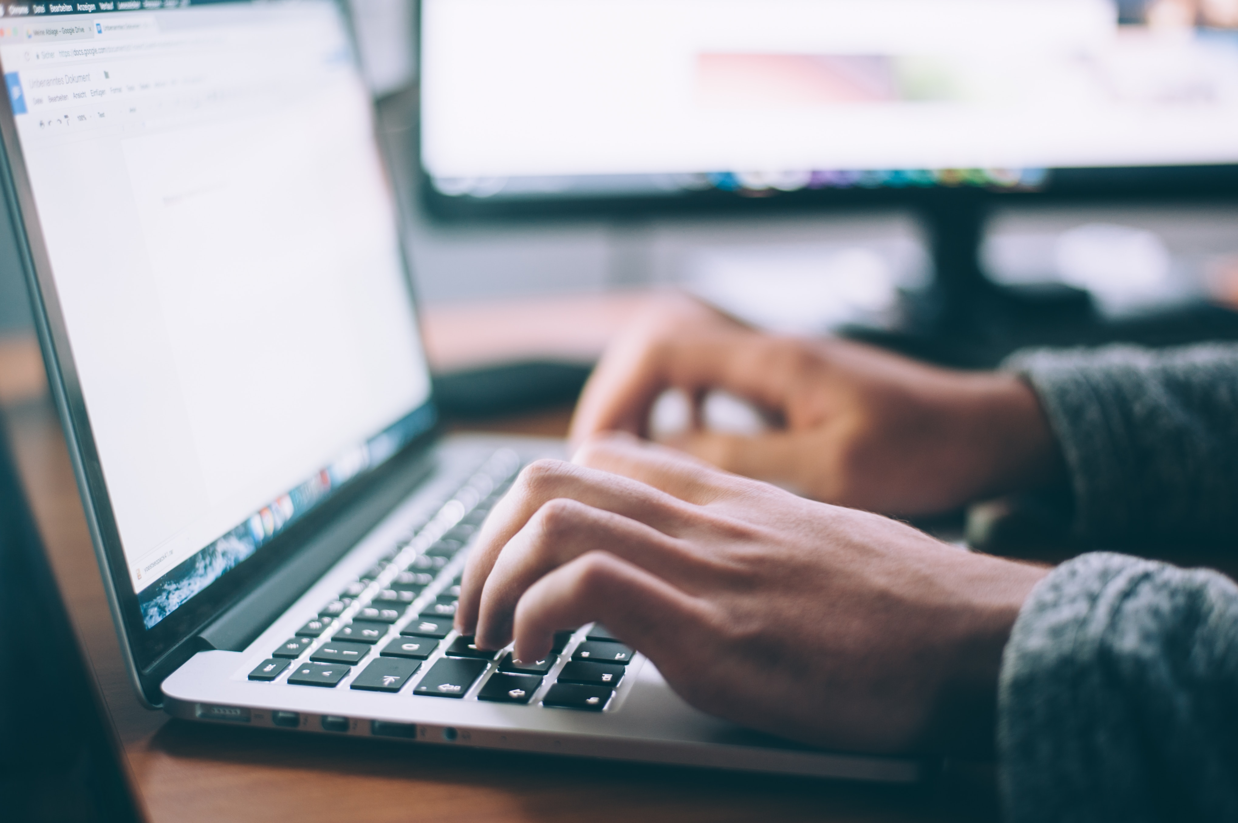 Macdator med händer på tangentbordet