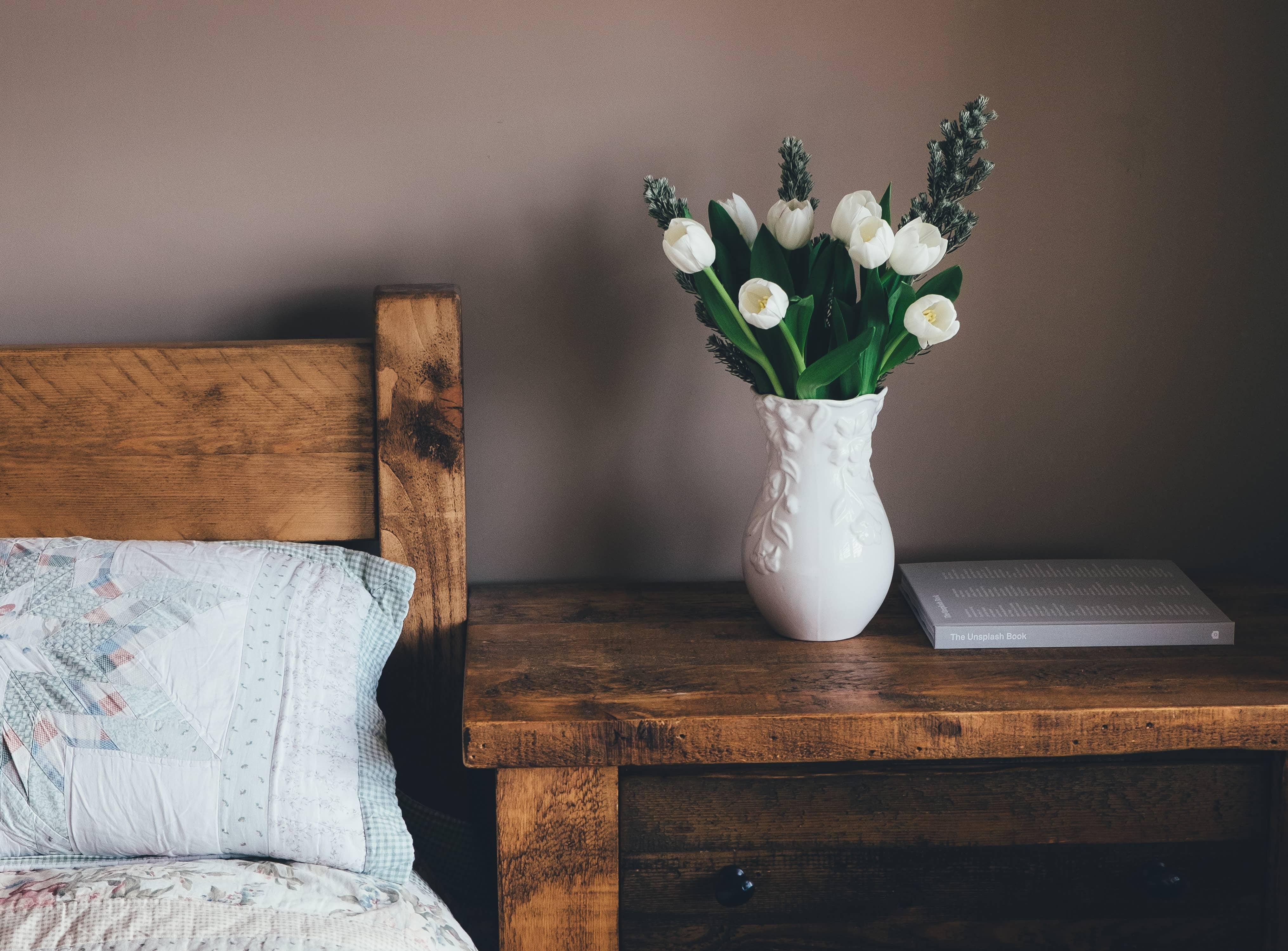 Blomvas på nattduksbord bredvid säng