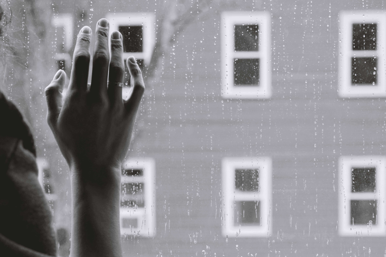 Person med ryggen till som tittar ut genom fönster
