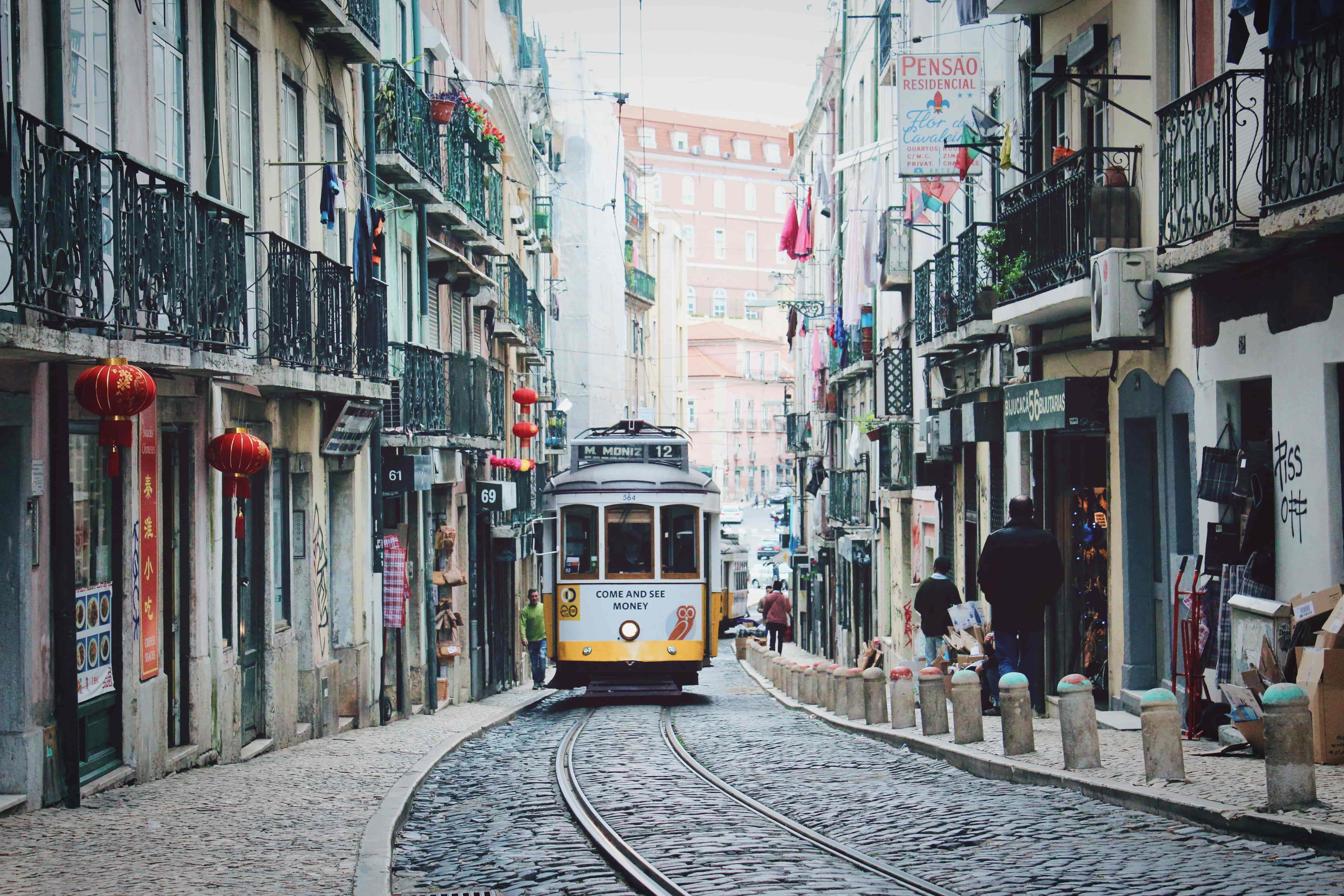 Gul spårvagn åker längs smal gata i Lissabon, en perfekt destination att flytta utomlands till