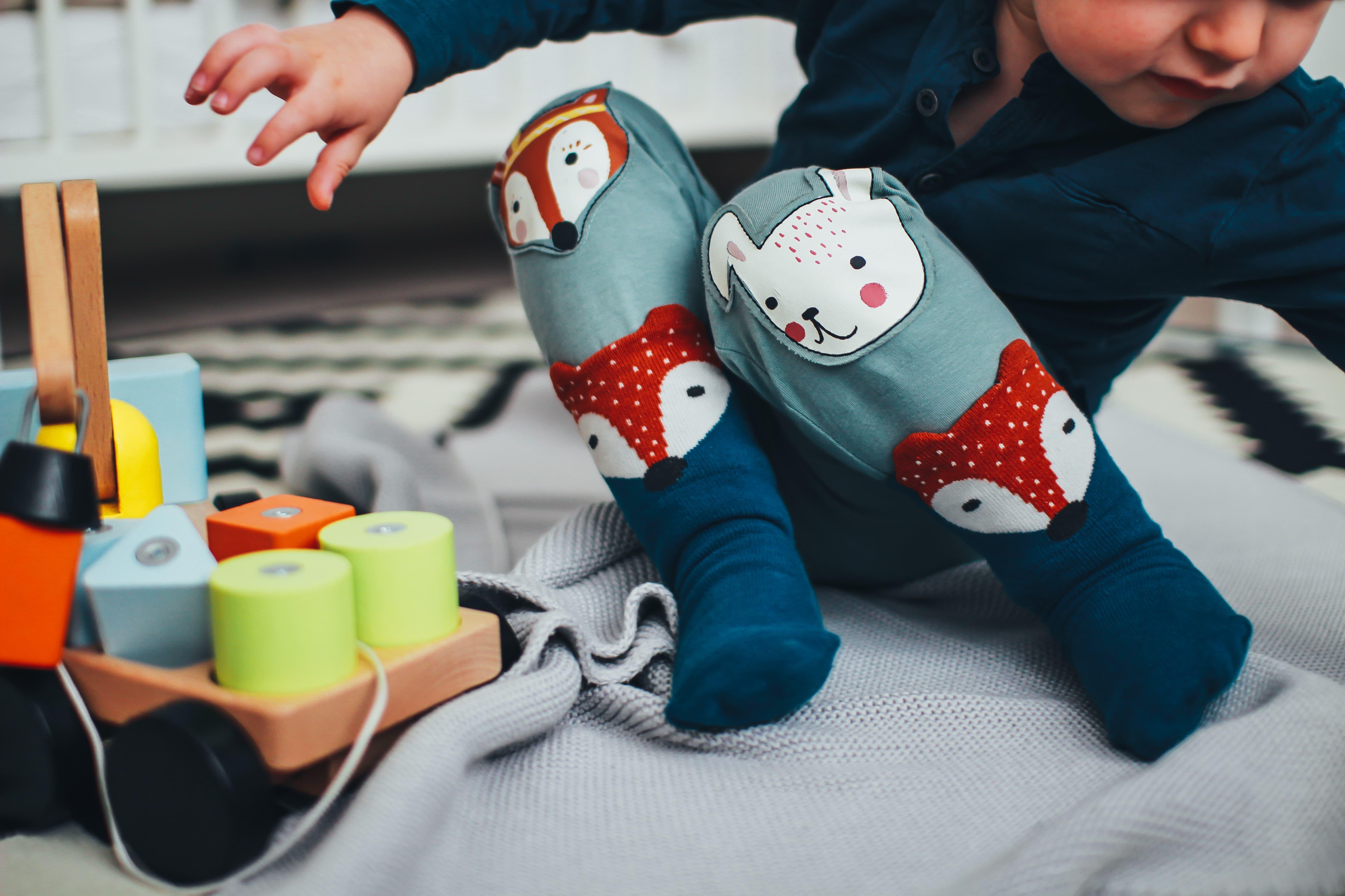 Pojke med djurmönstrade byxor och blå strumpor leker med klossar. Kommunikation är A och O när det kommer till att flytta med delad vårdnad.