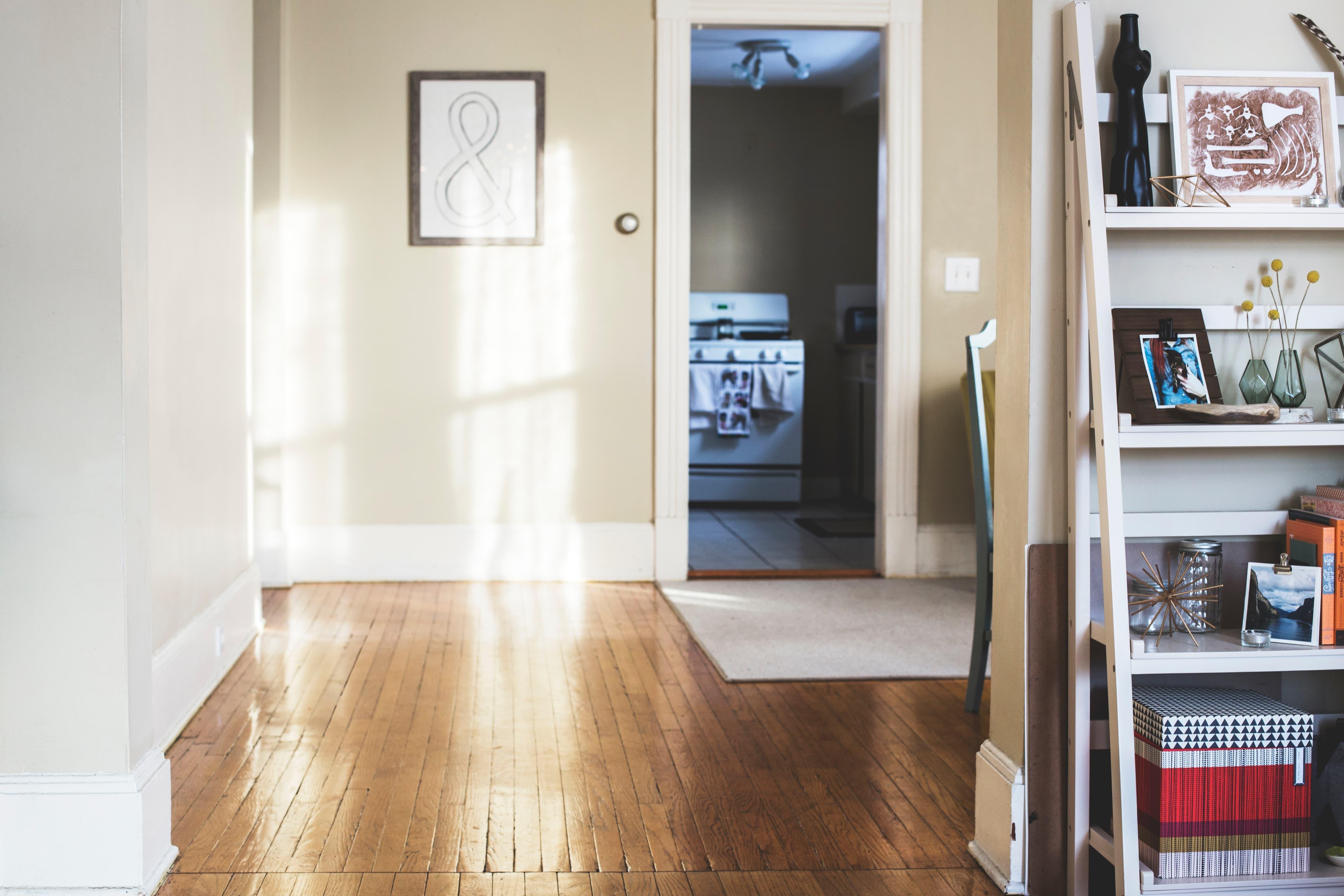 Vardagsrum med bokhylla och tavla på väggen, innan besiktning av lägenhet
