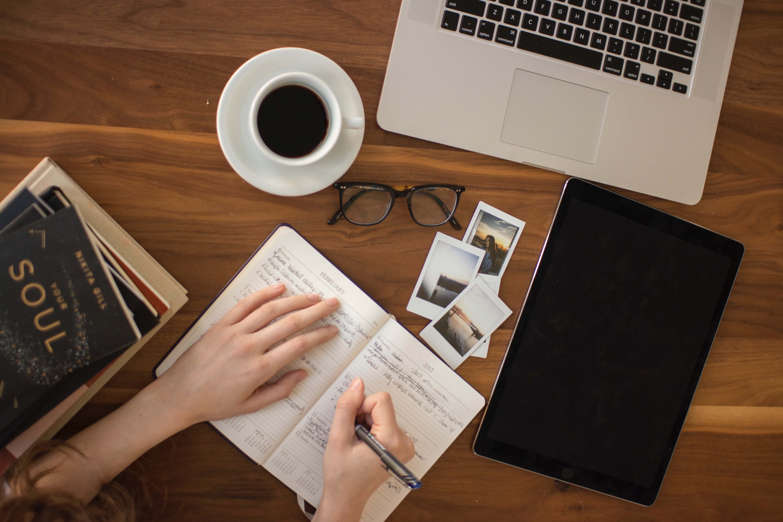 Hand som håller i penna vid  anteckningsbok och dator