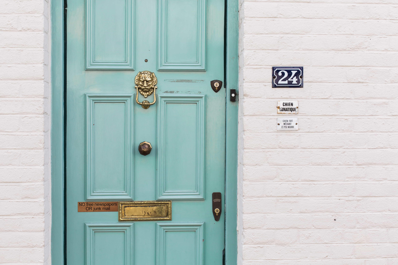 Vit tegelvägg med turkos dörr med guldfärgad lejonformad dörrknackare, till lägenhet som fåtts genom förstahandskontrakt.