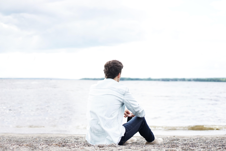 Man i vit skjorta sittande på strand, överväger sitt beslut att flytta isär.
