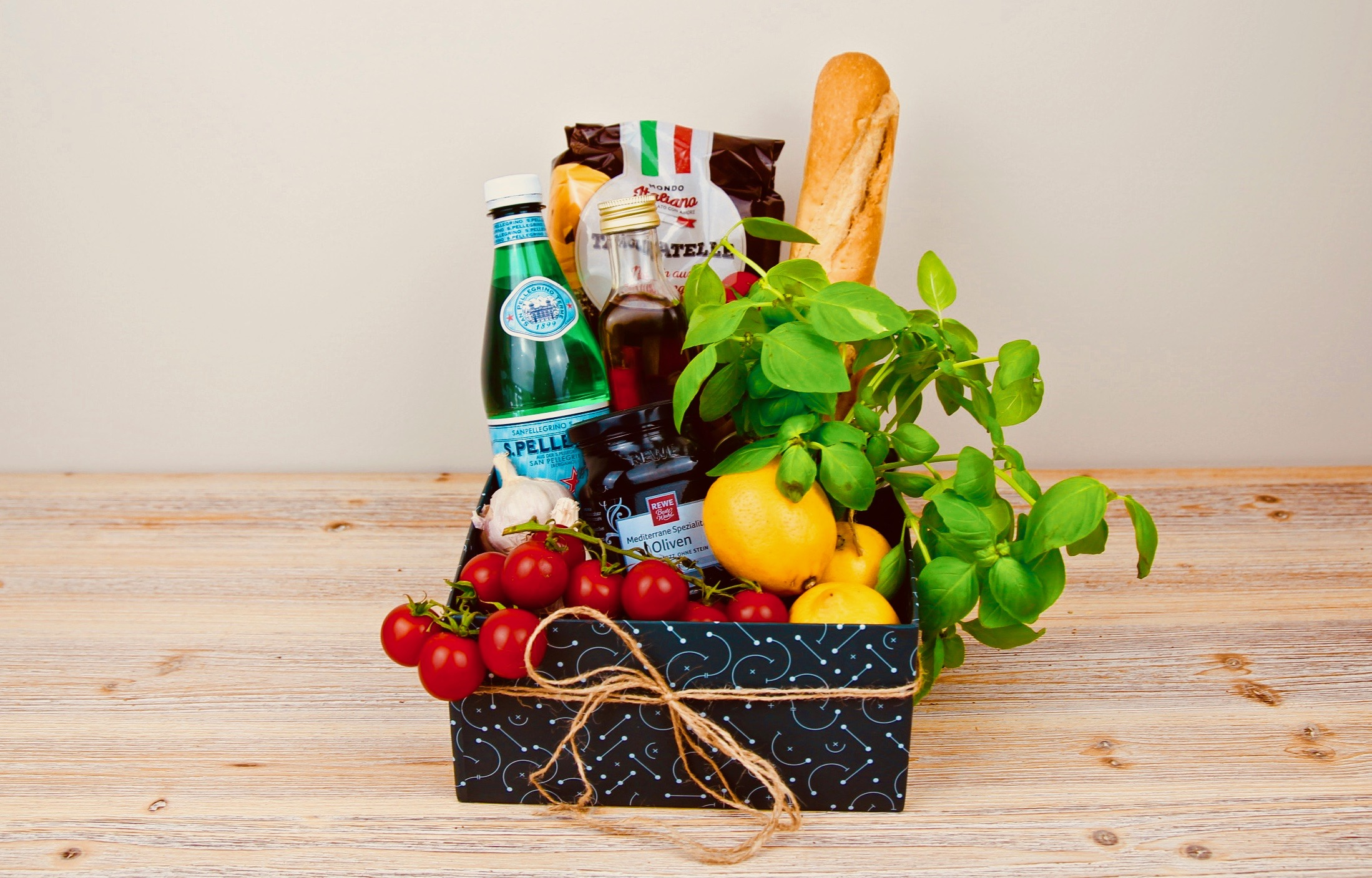 Presentkorg med pasta, tomater och basilika för medelhavspasta