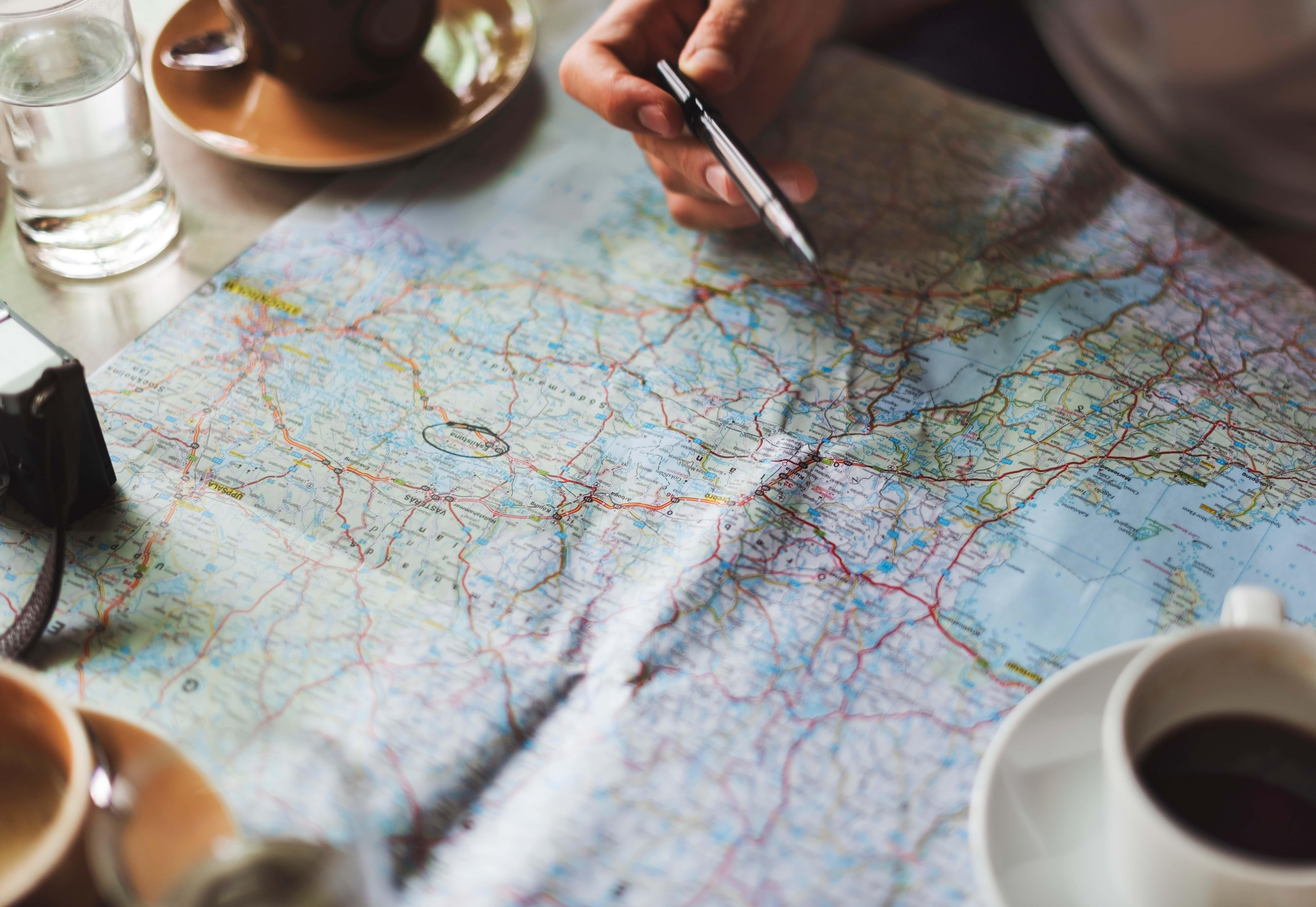 Hand som håller i penna ovanför karta