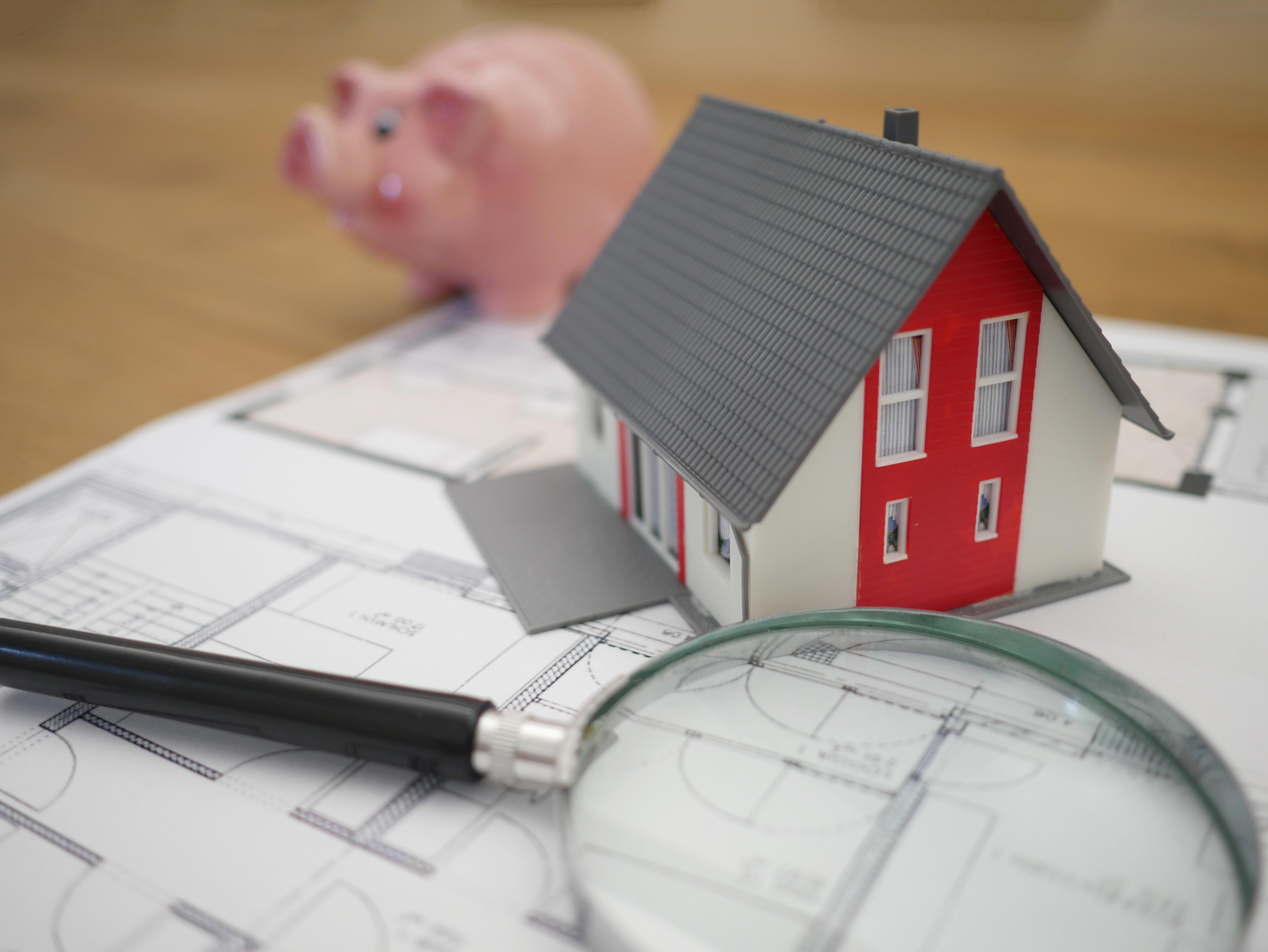 Miniatyrhus, förstoringsglas och spargris stående på planritning. Flyttfirma pris påverkas bland annat av avstånd mellan ny och gammal adress
