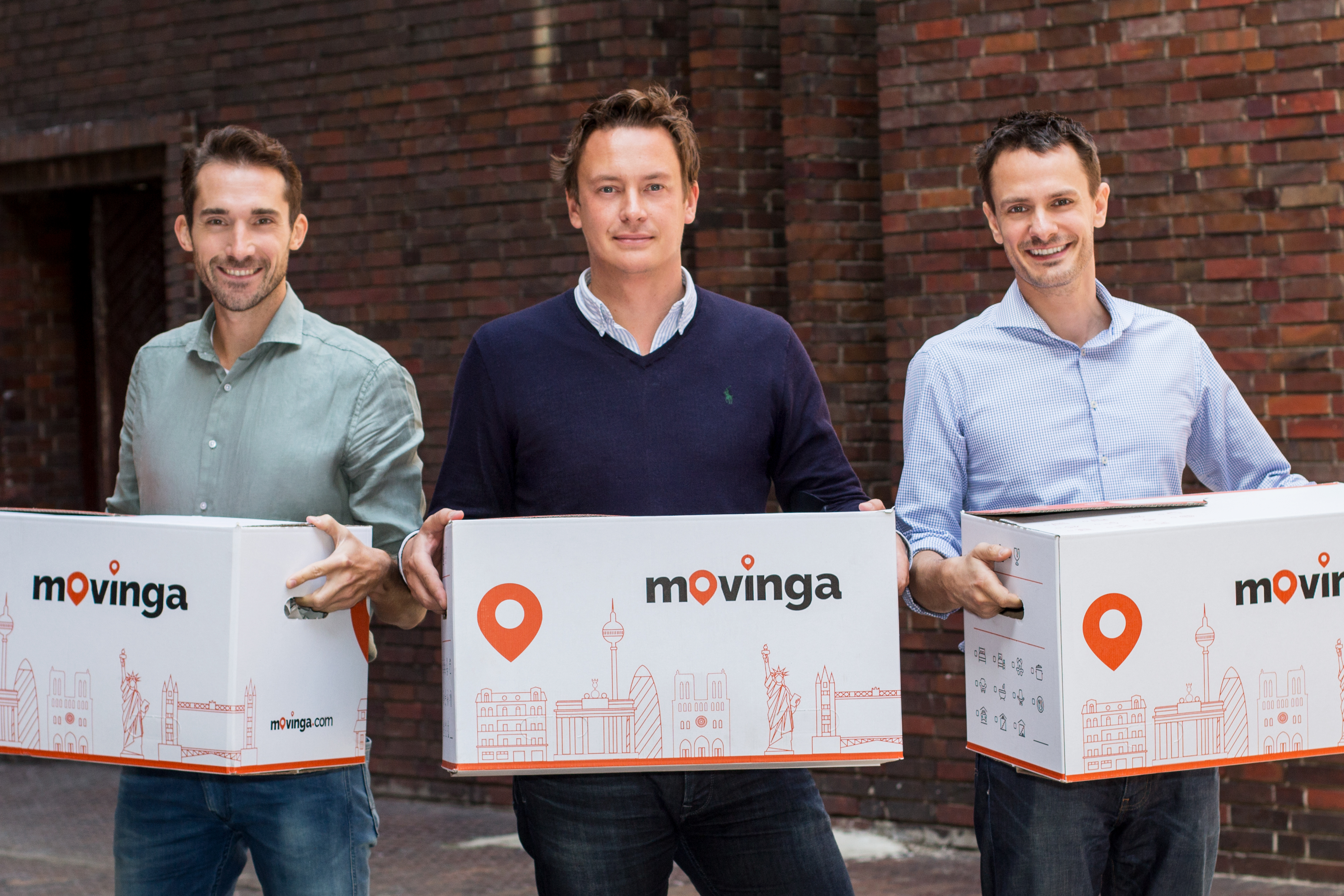 picture of 3 men holding movinga labelled boxes.