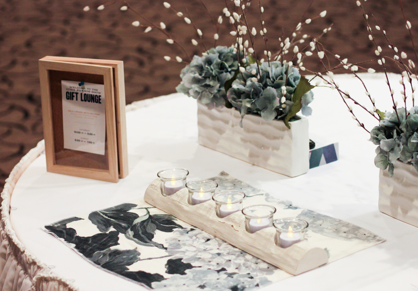 Candles and flower arrangements on a gift lounge table
