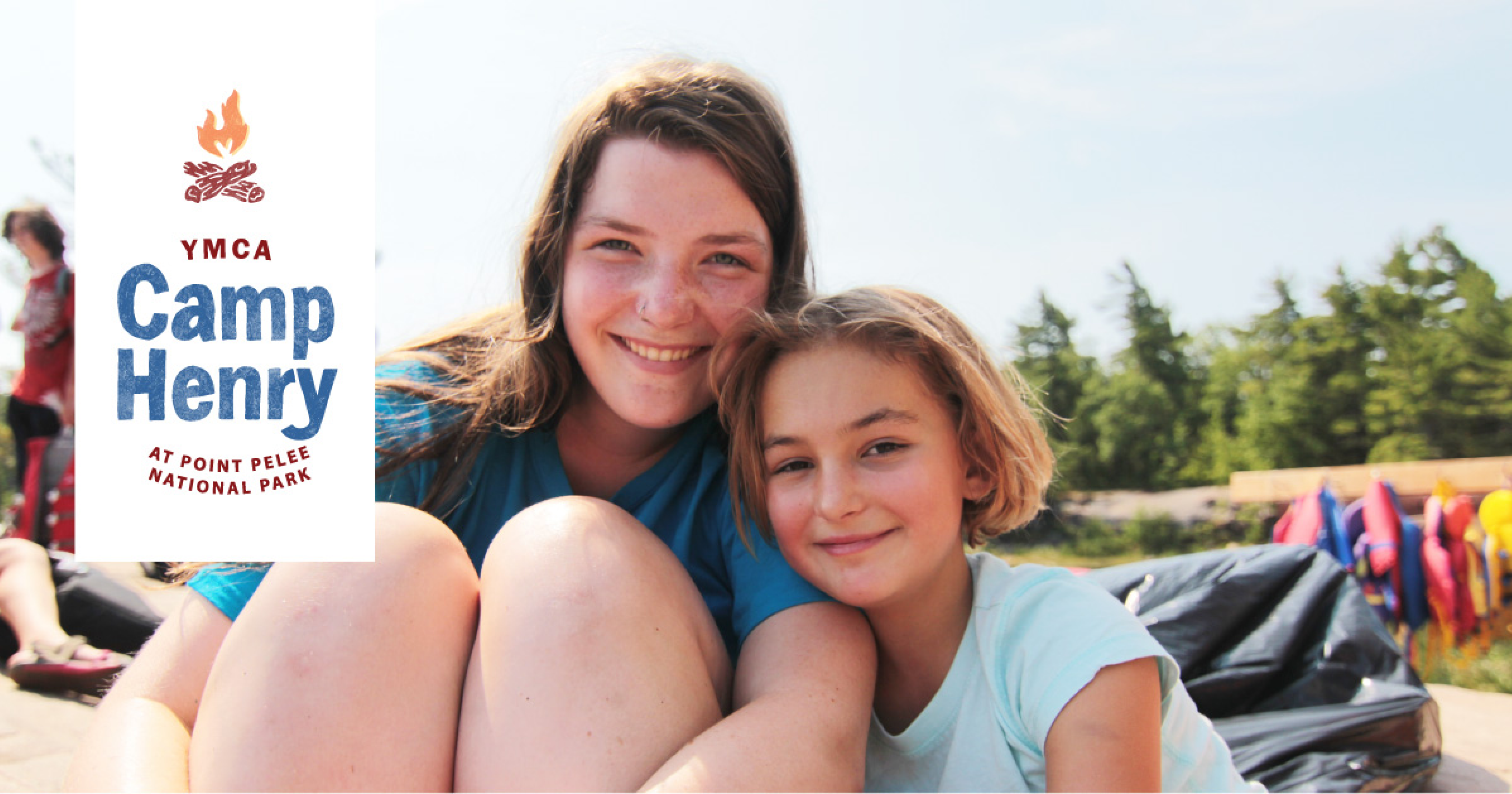 Camper and camp counsellor smiling at the beach