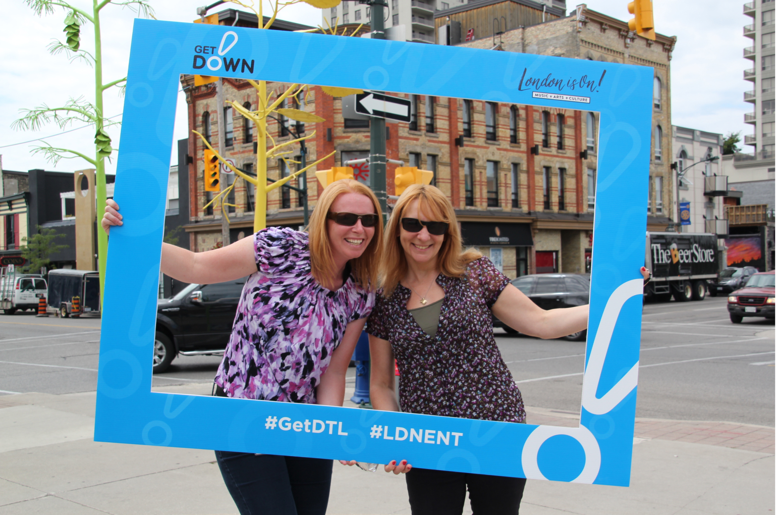 Two women posing with the #GetDTL photo frame