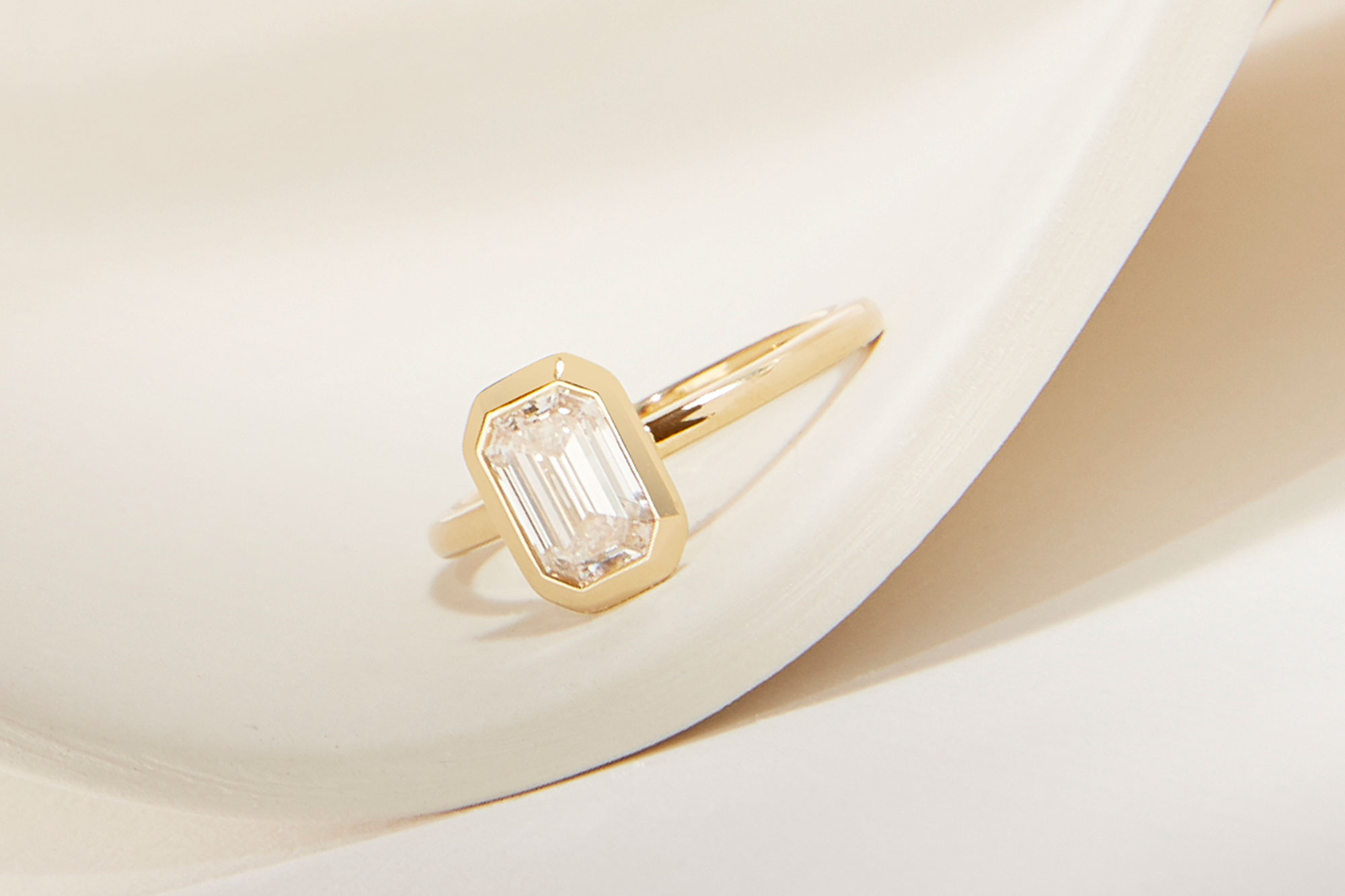 The emerald signature bezel engagement ring with yellow gold band
