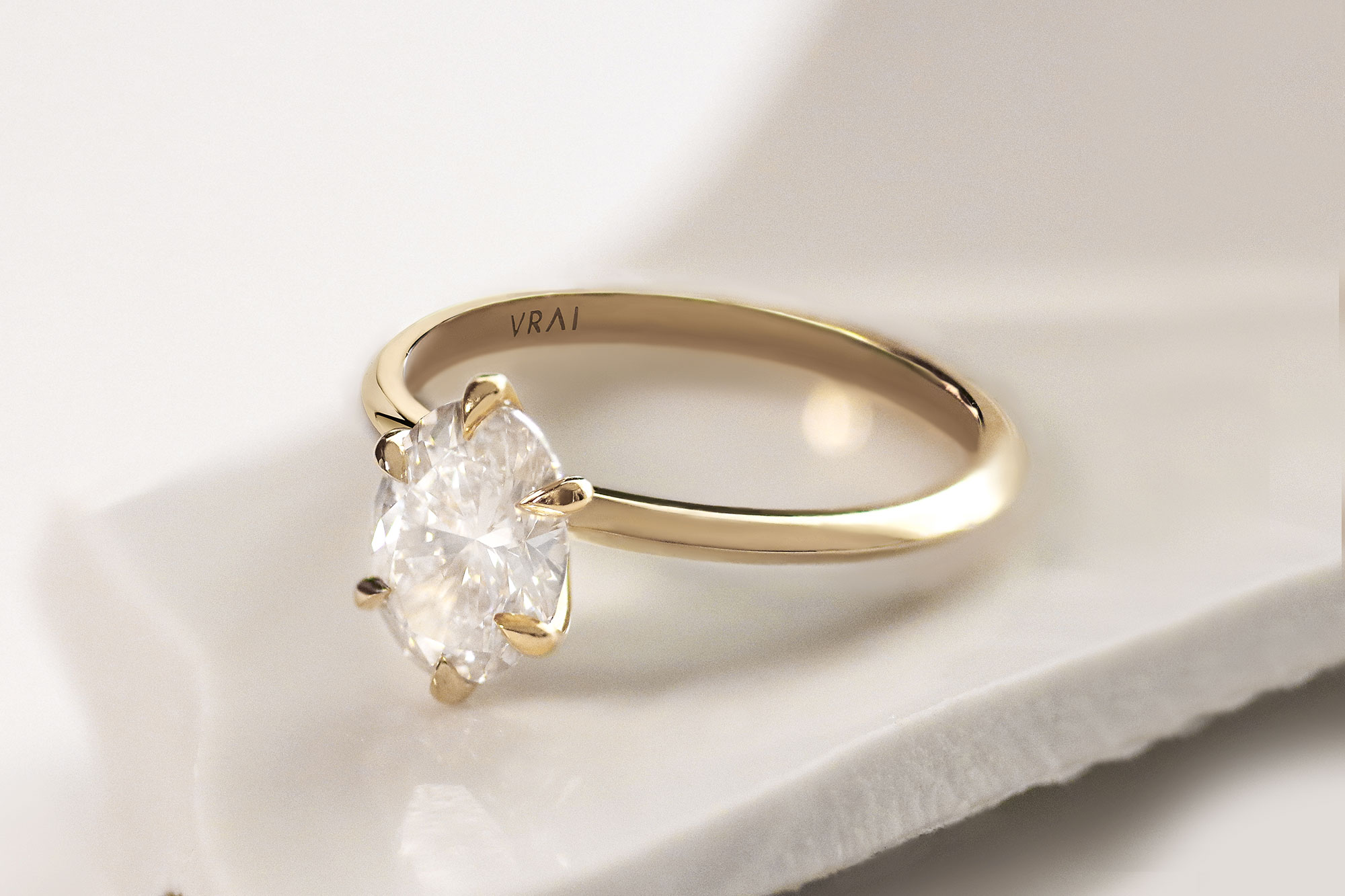 The oval knife edge engagement ring with yellow gold band