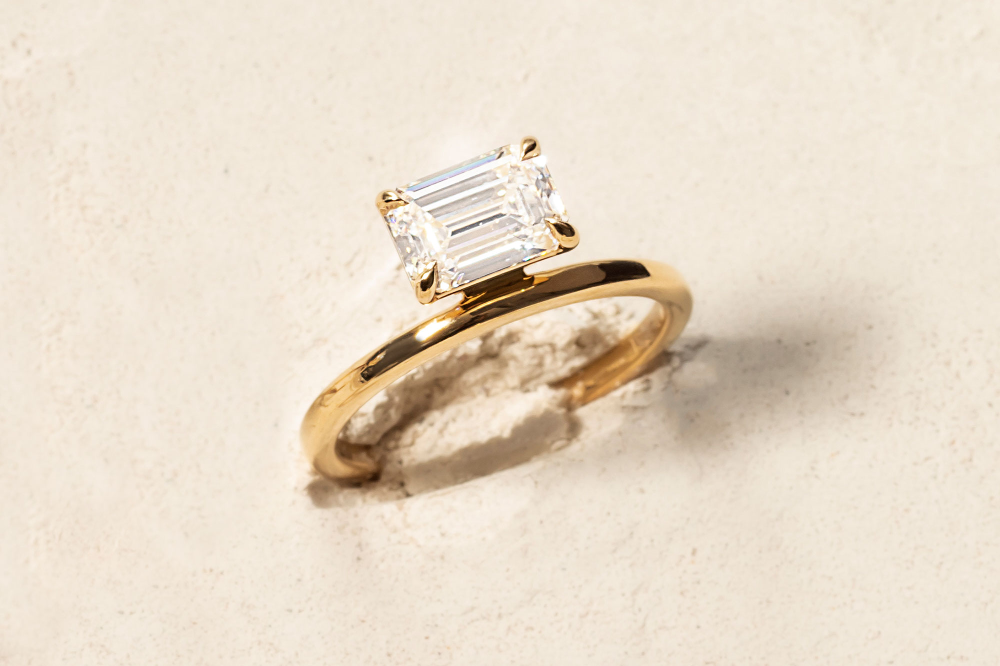 the emerald hover engagement ring with yellow gold band