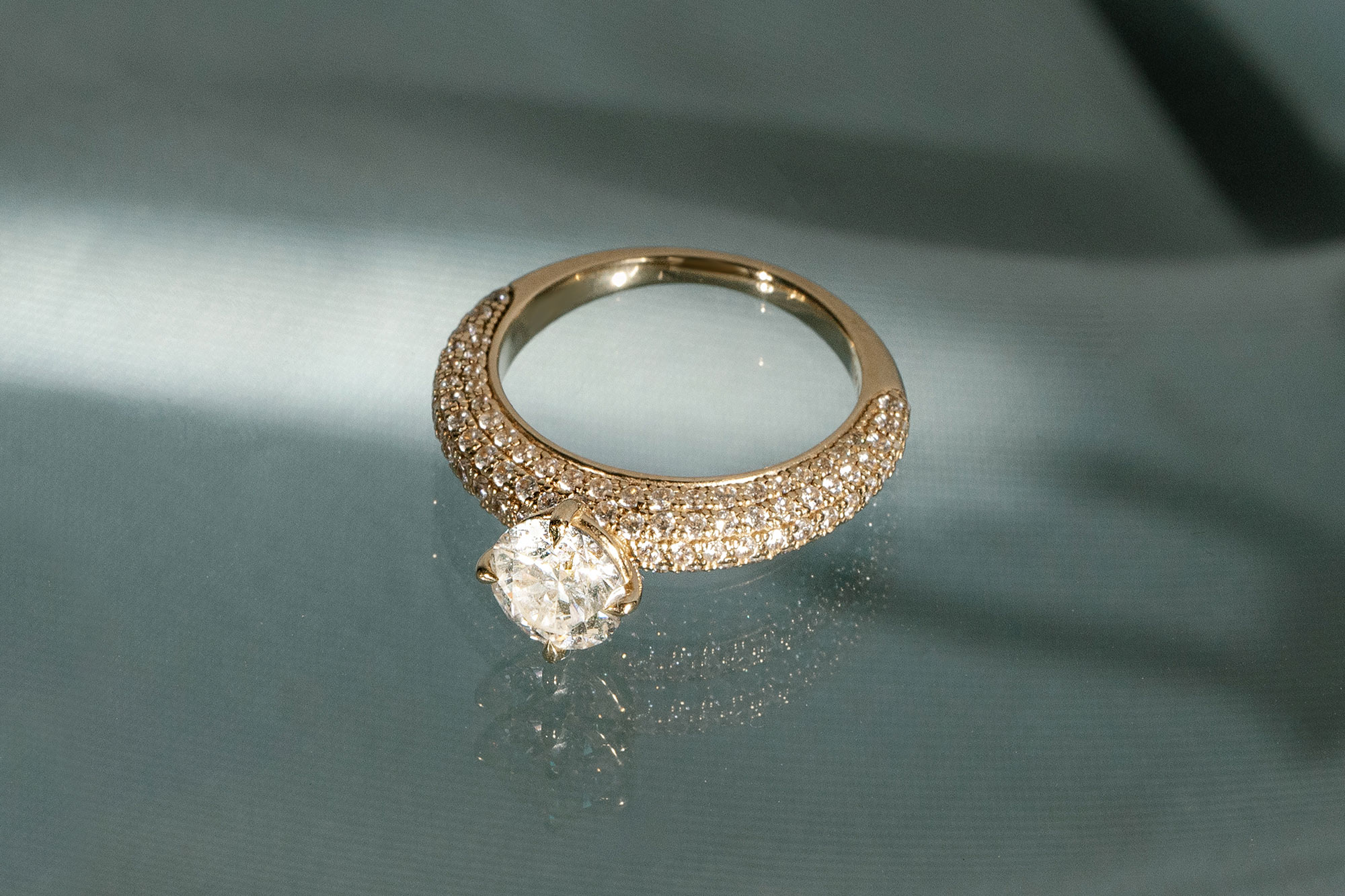 the round brilliant curator engagement ring with yellow gold pave band