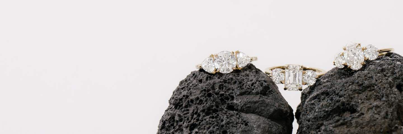 Three diamond engagement rings sitting on two stones.