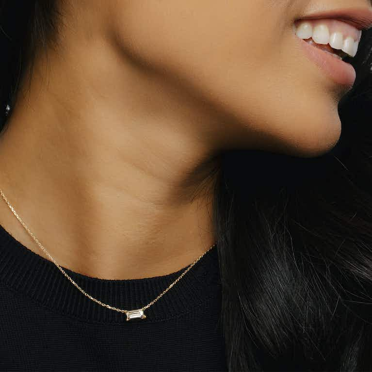 golden necklace with a baguette shaped diamond on a woman's neck
