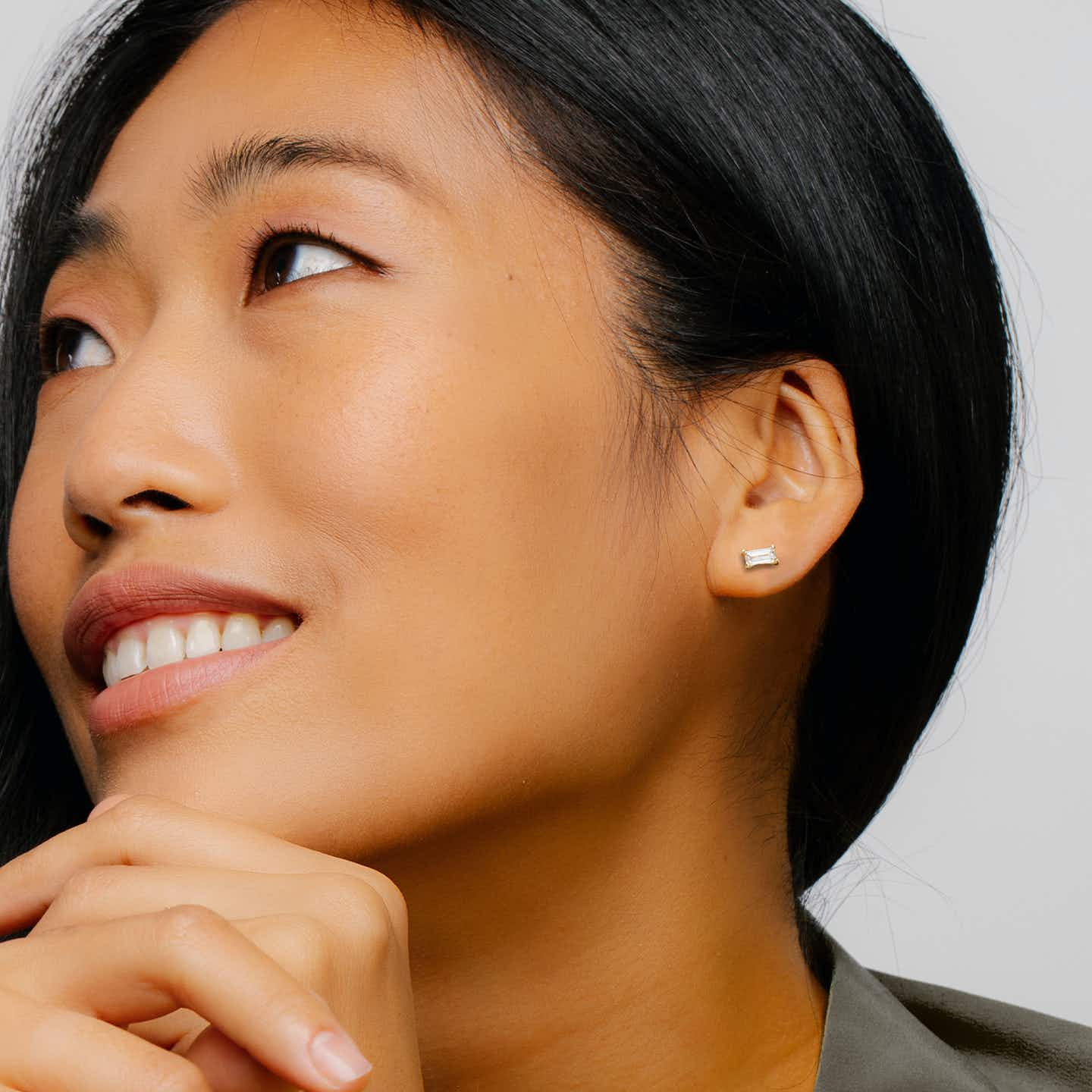 smiling woman shows a stud with a baguette shaped diamond on her left ear
