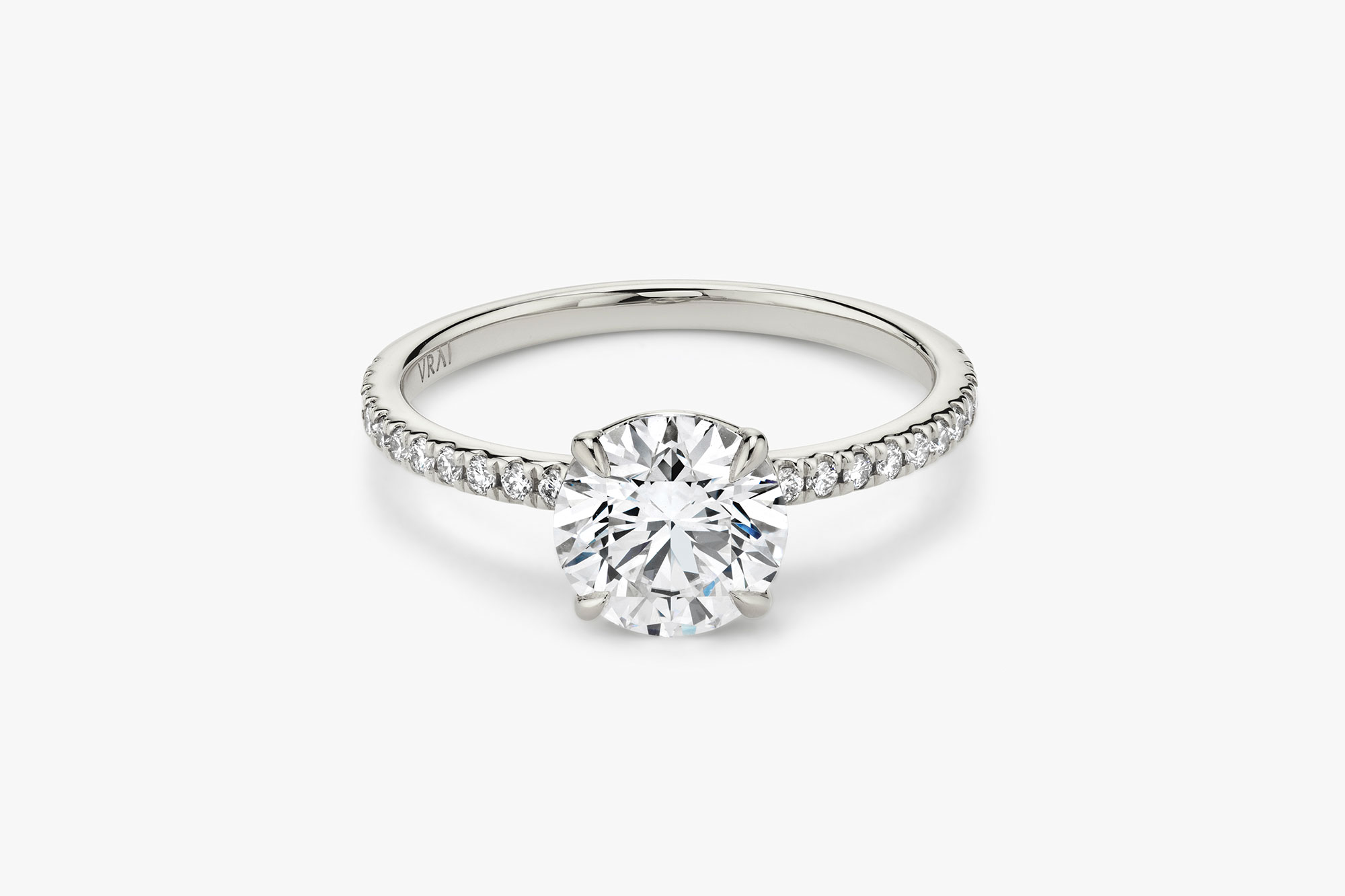 The Signature solitaire ring in 18k white gold with a round brilliant cut diamond and pavé band