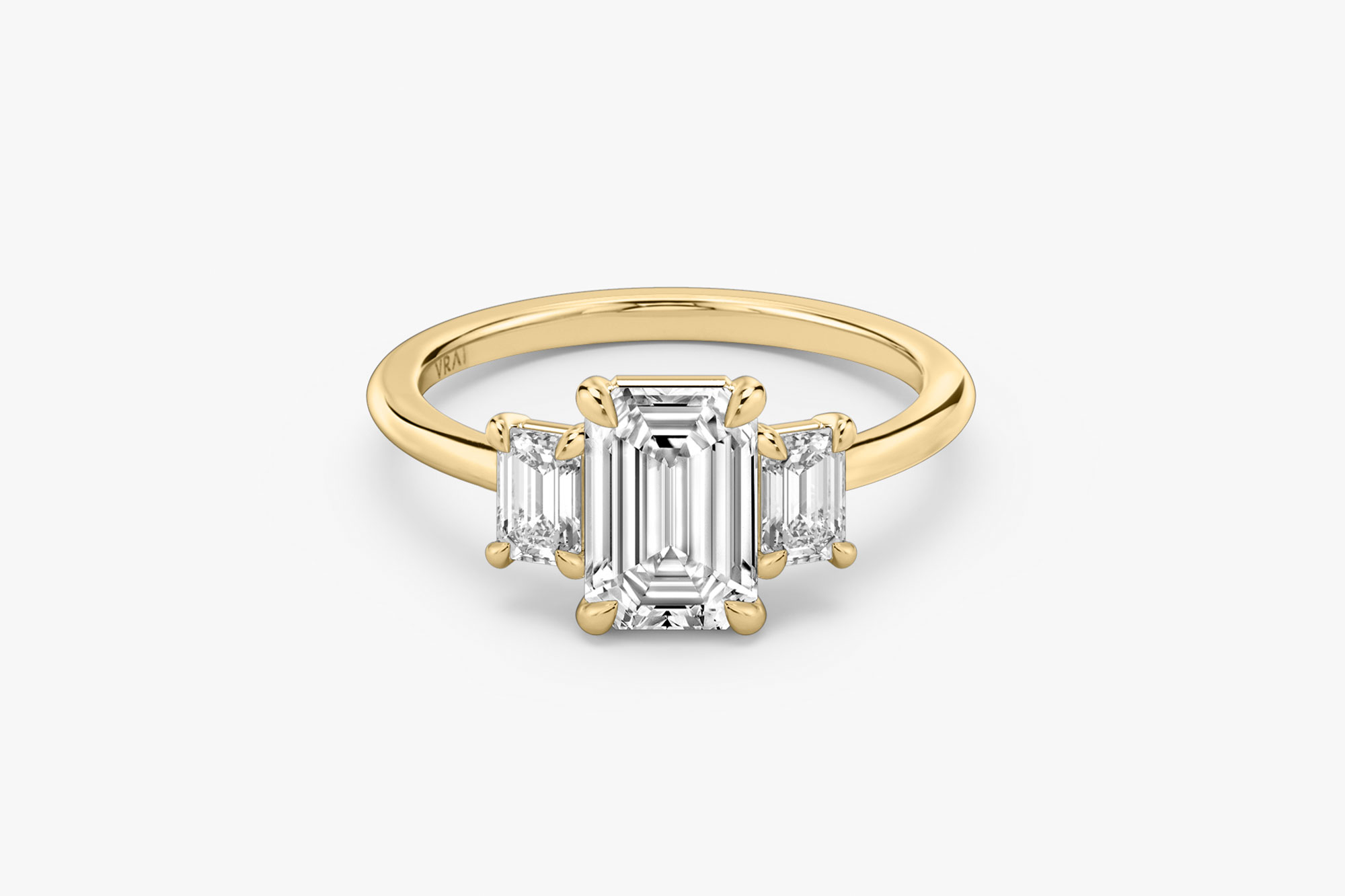 The Three Stone ring in 18k yellow gold with an emerald cut diamond