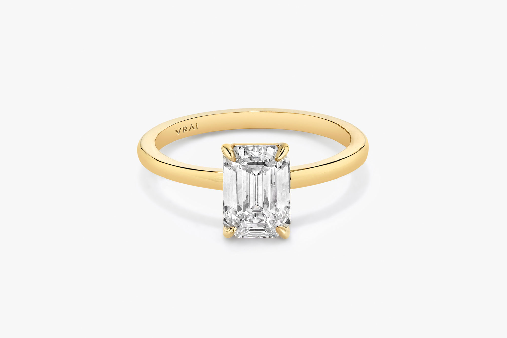 The Signature solitaire ring in 18k yellow gold with an emerald cut diamond