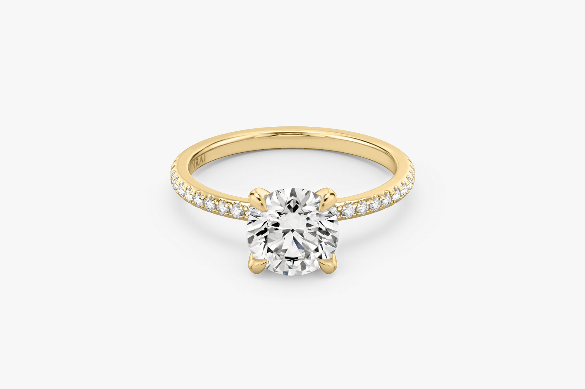 The Classic solitaire in 18k yellow gold with a round brilliant cut diamond and pavé band