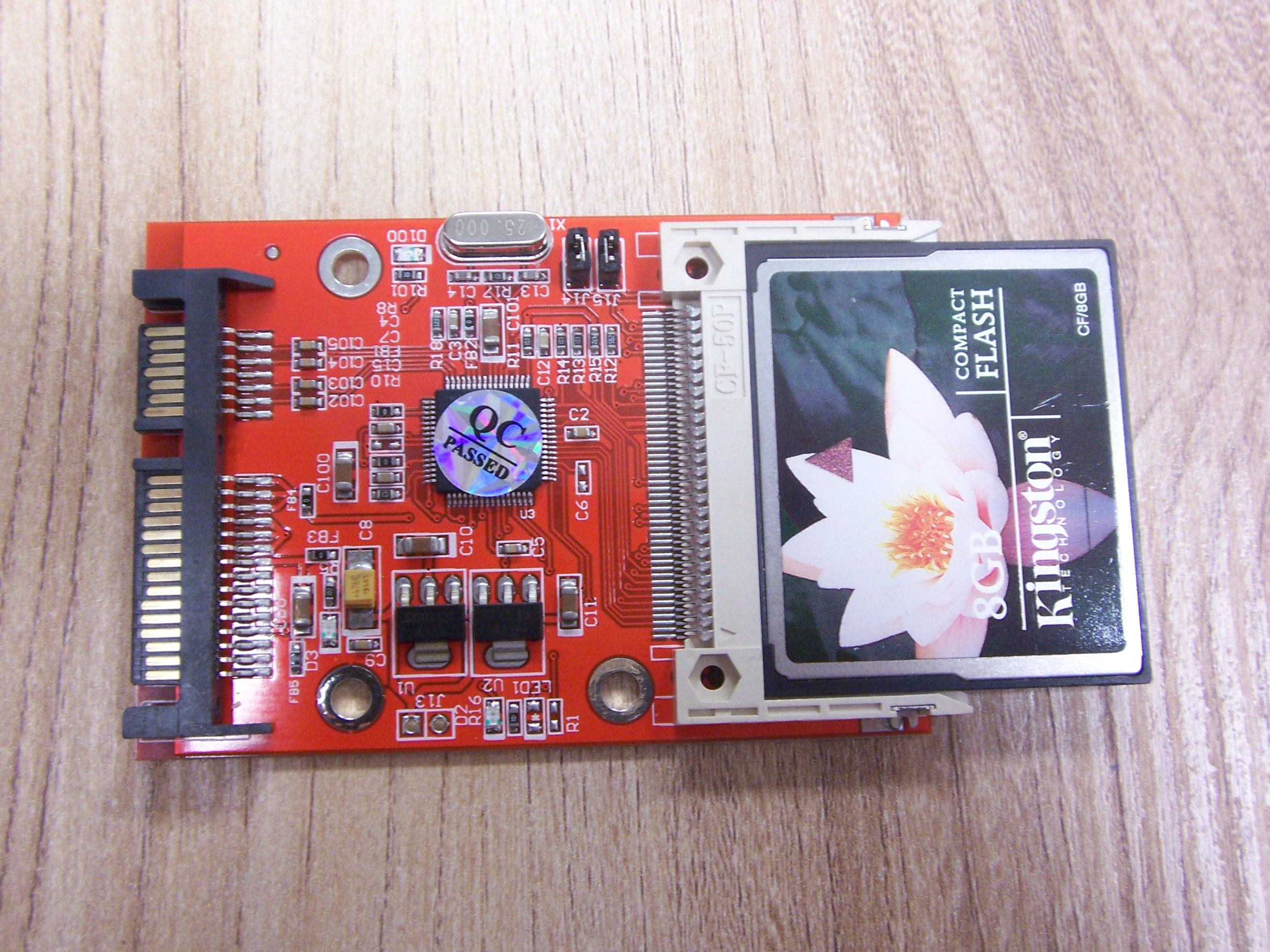 Przejściówka SATA - CompactFlash, widoczne złącze SATA i slot CF z zainstalowaną kartą.