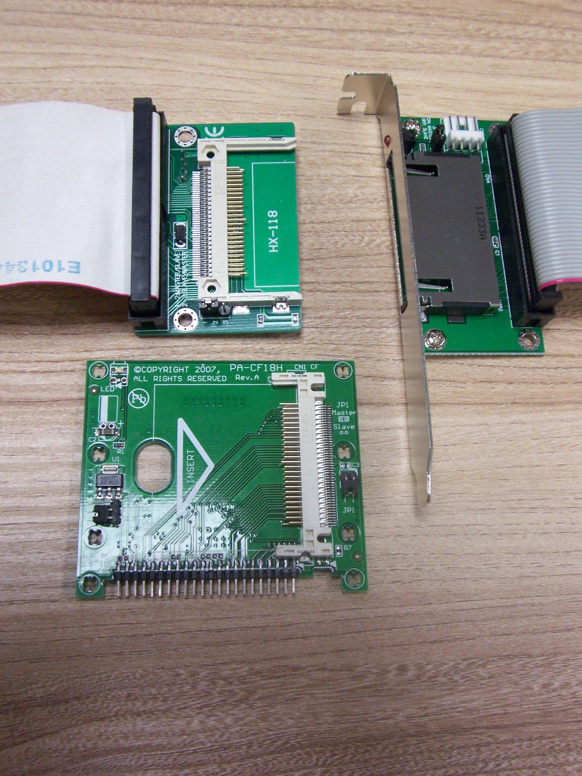 Trzy przejściówki CF - PATA (IDE): po lewej wewnętrzna, przyłączona do taśmy 80-żyłowej, po prawej zewnętrzna, na śledziu montażowym z taśmą 40-żyłową, pod nimi przejściówka w formacie 2,5 cala, ze złączem IDE 44 pin