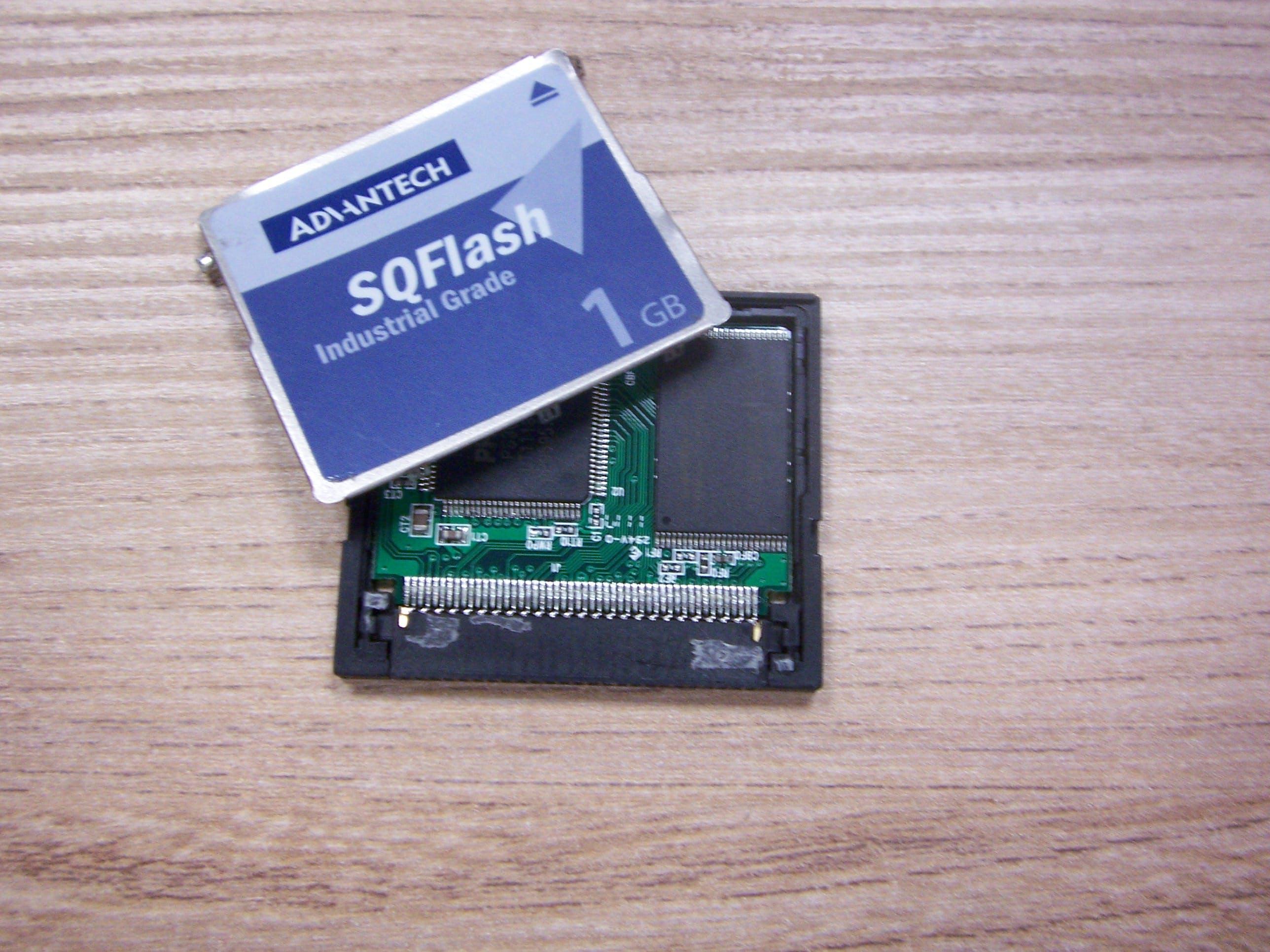 Przemysłowa karta CF z otwartą obudową,widoczny kontroler i pamięć flash