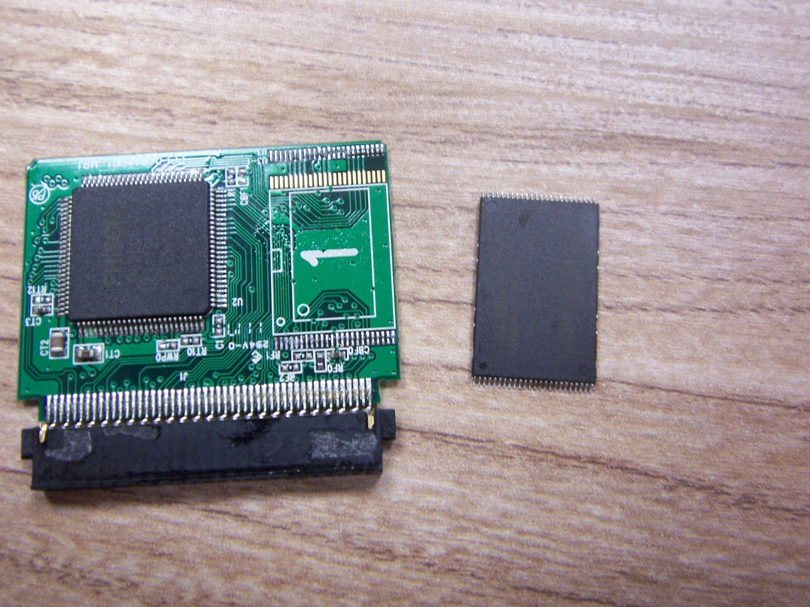 Odlutowany Chip NAND Flash obok płytki drukowanej karty CF, na płytce nadal przylutowany kontroler pamięci flash