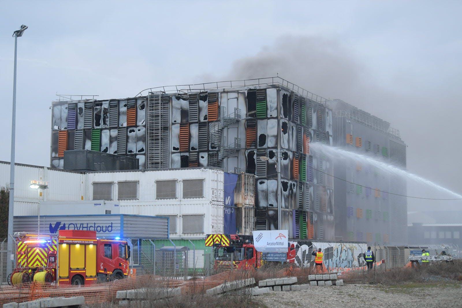 Dogaszanie spalonego budynku serwerowni, widać strumień środka gaśniczego i wozy strażackie na pierwszym planie.