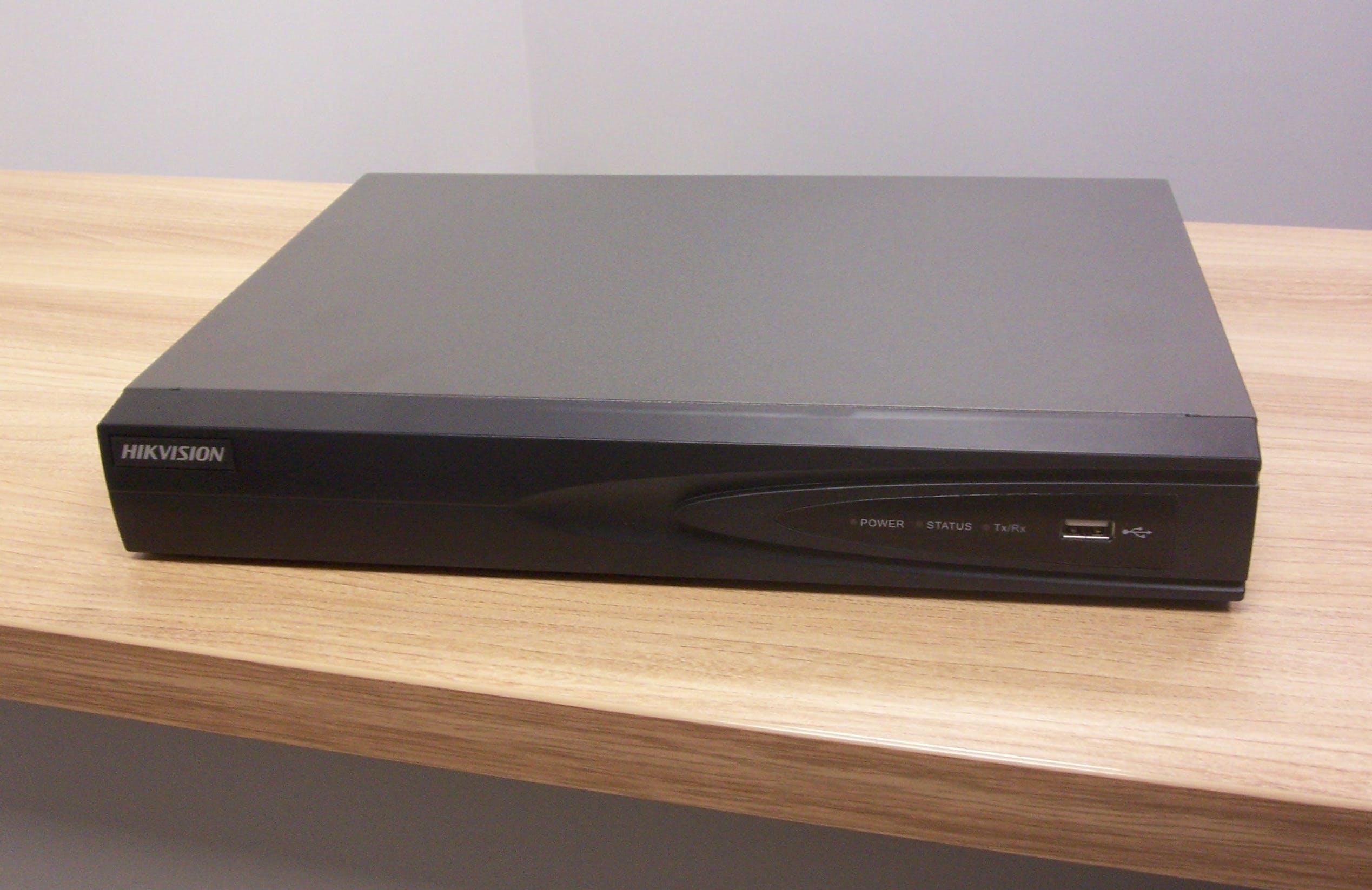 Rejestrator firmy HIKVISION w czarnej obudowie. Po lewej widoczne logo producenta, po prawej port USB i diody komunikujące stan urządzenia.