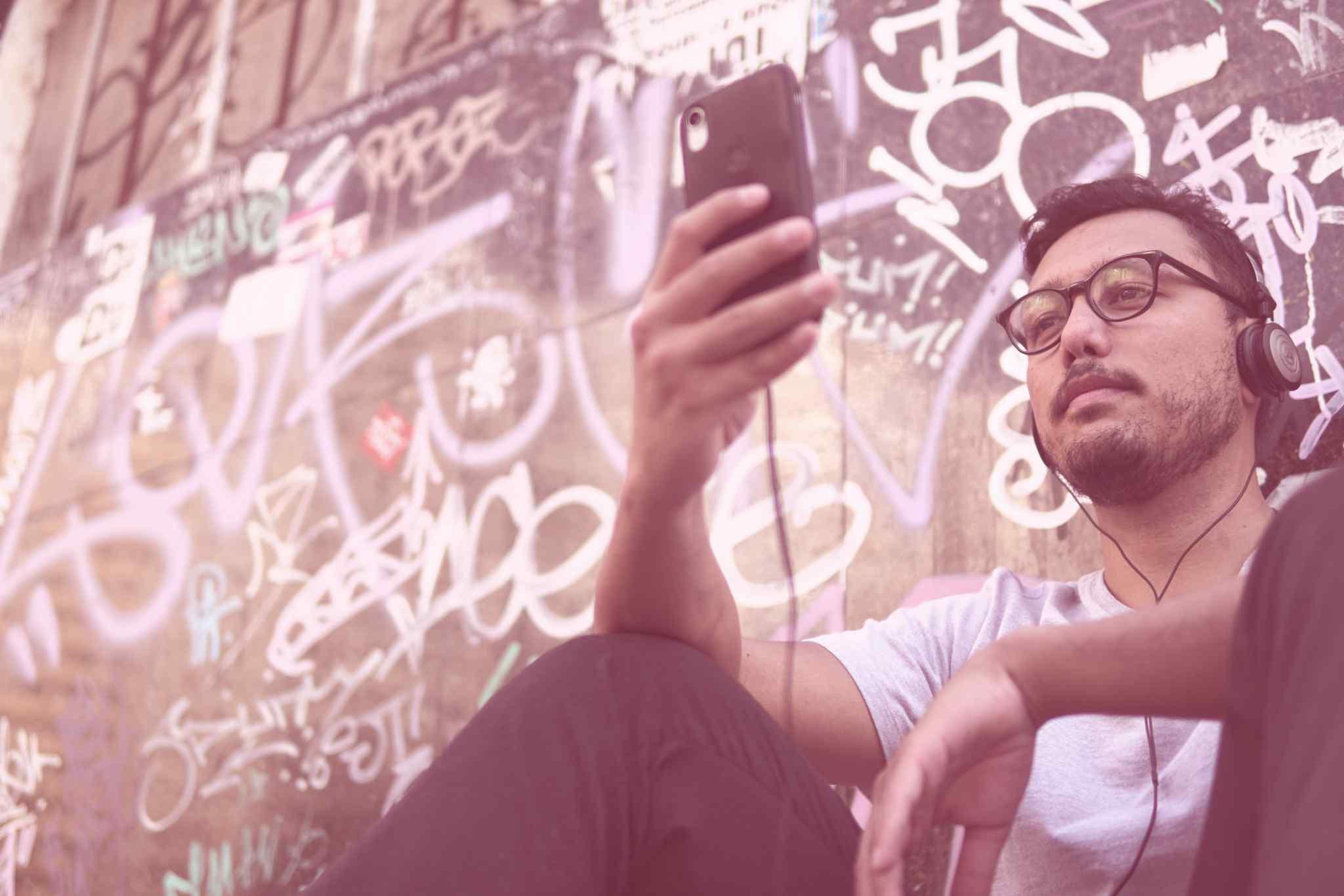 Pessoa segurando smartphone em frente a uma parede grafitada.